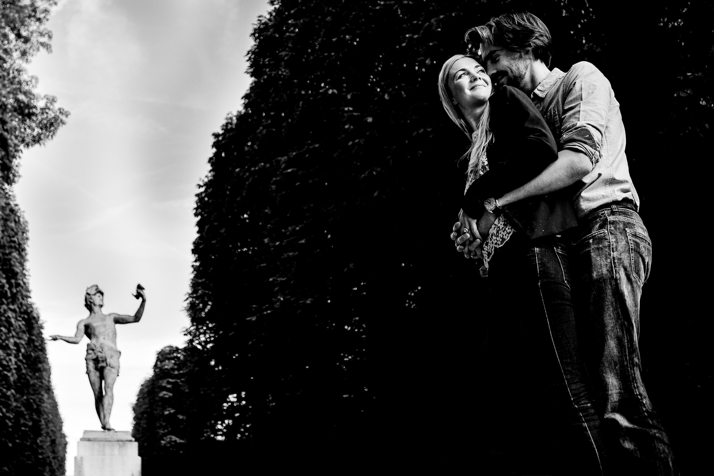 A peaceful moment of connection during Faye and David's Montmartre Paris Engagement date in the Luxembourg Gardens near a historic statue