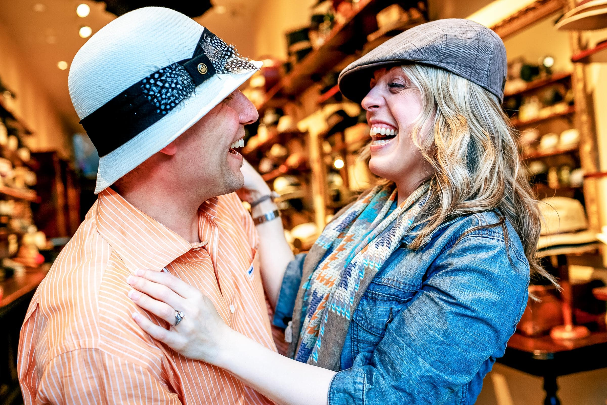 A fun laughing couple wearing hats along Northwest Nob Hill during their Portland Engagement Date