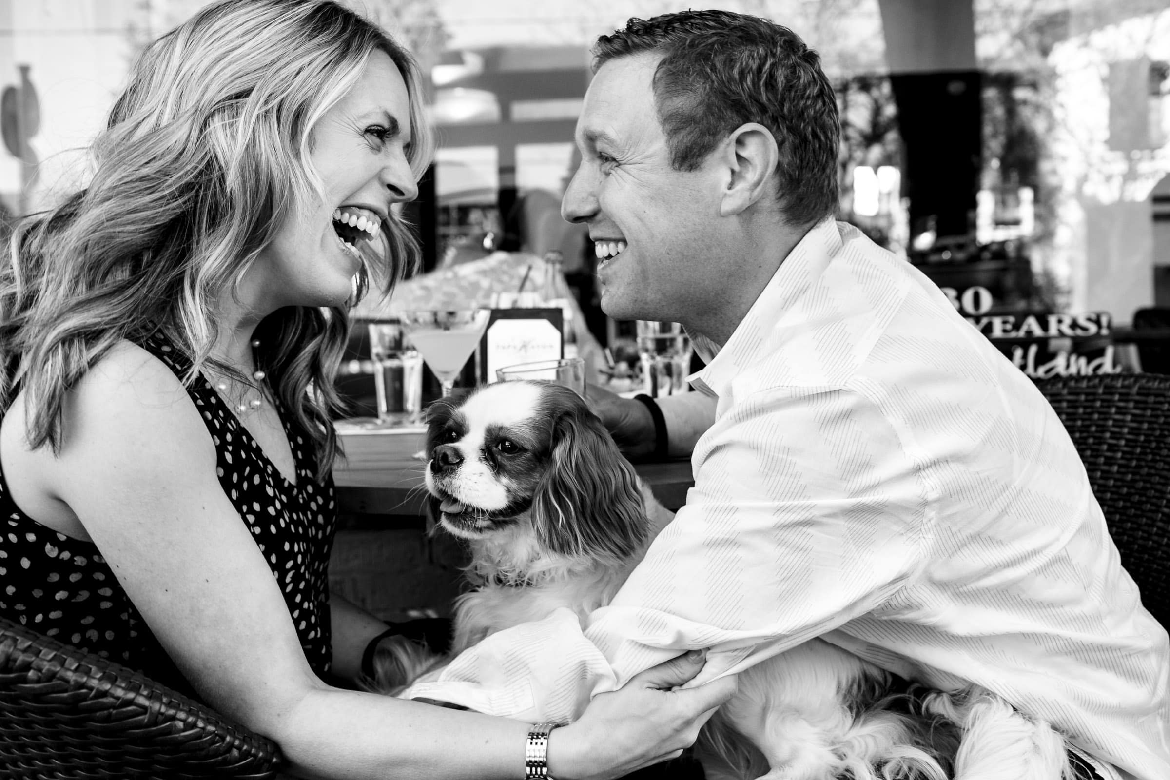 A fun laughing couple enjoying their dog and food at Papa Haydens along Northwest Nob Hill during their Portland Engagement Date