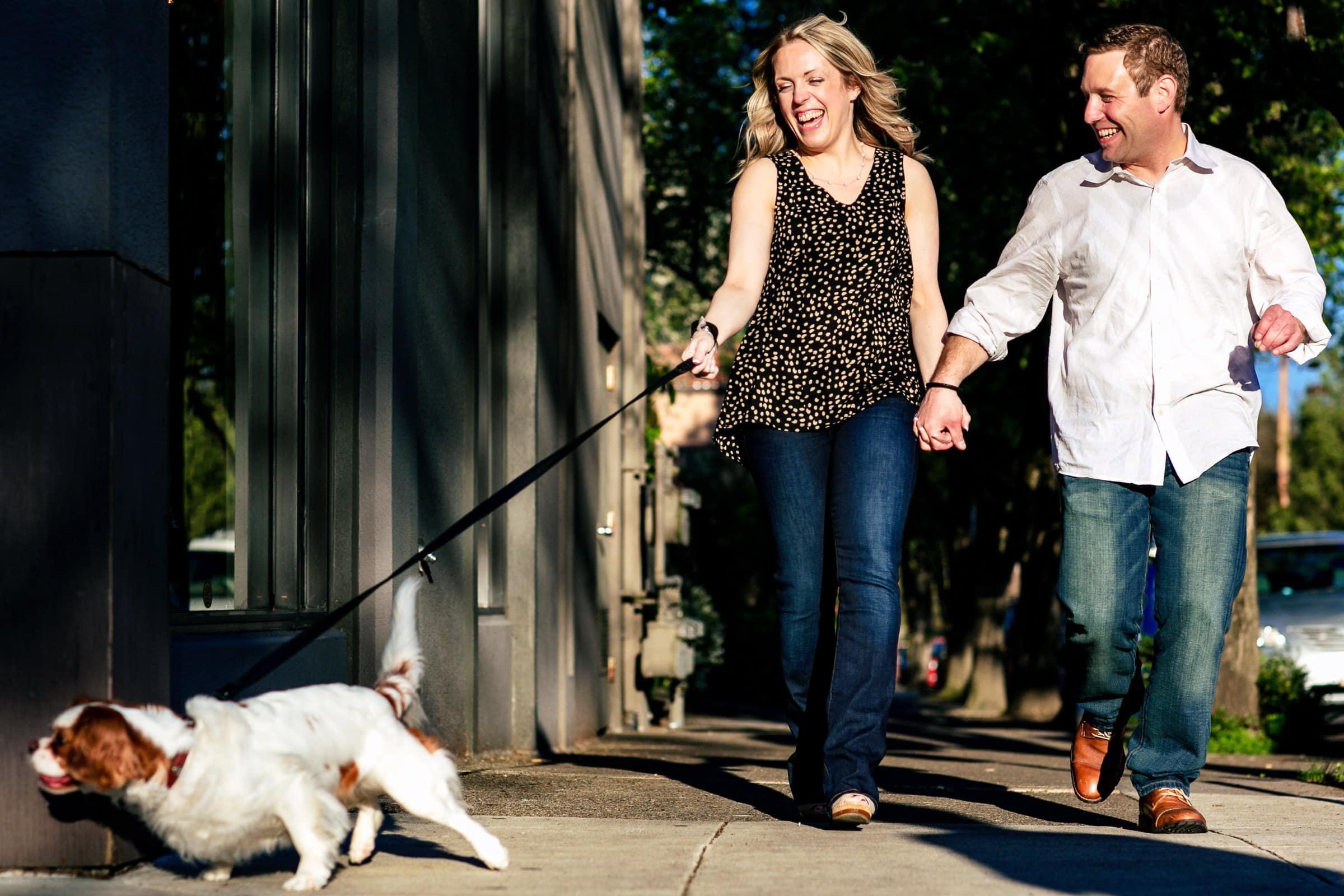 A fun laughing couple walking their dog along Northwest Nob Hill during their Portland Engagement Date