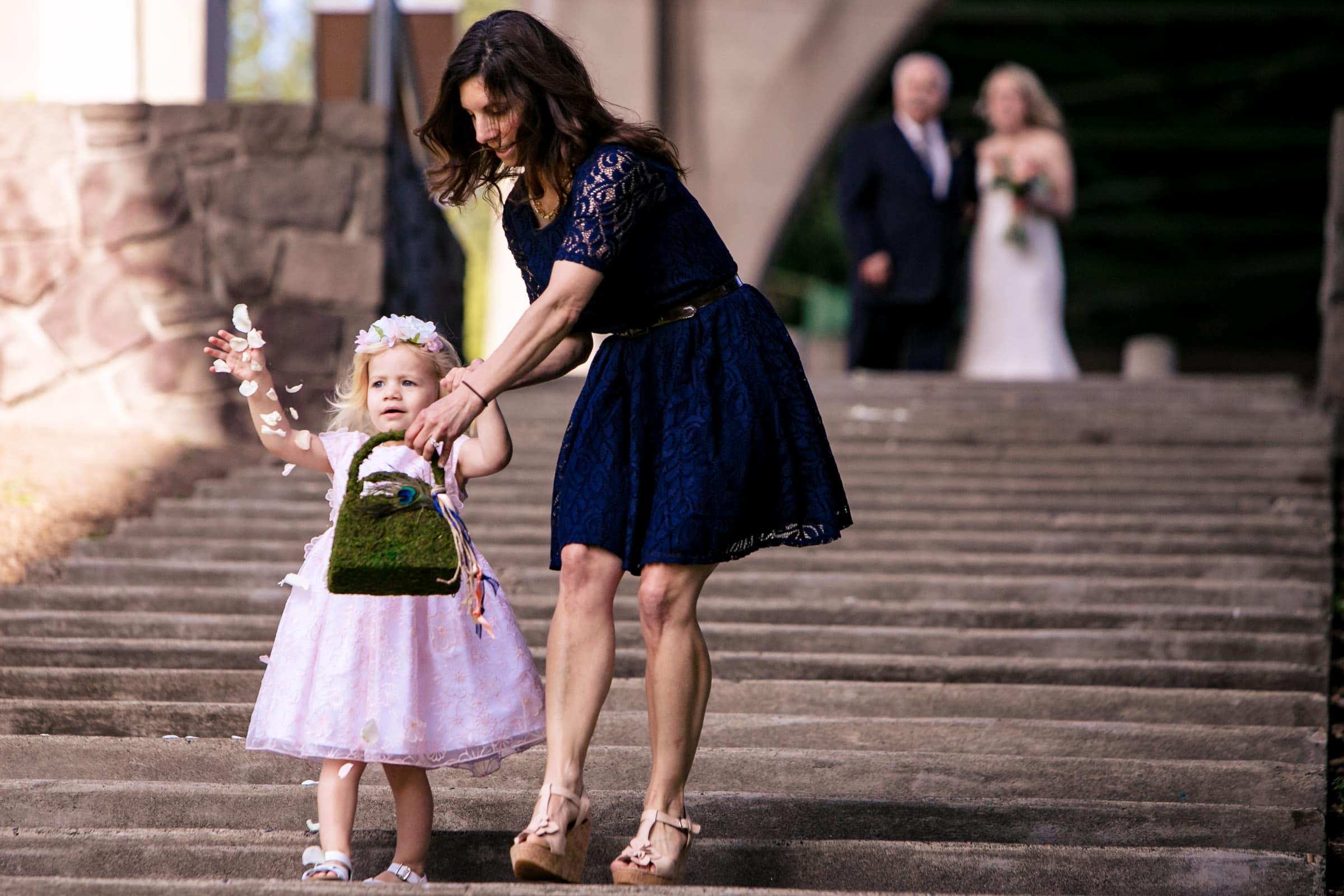 Flower girl walking into an outdoor small Cathedral Park Wedding ceremony in Portland Oregon