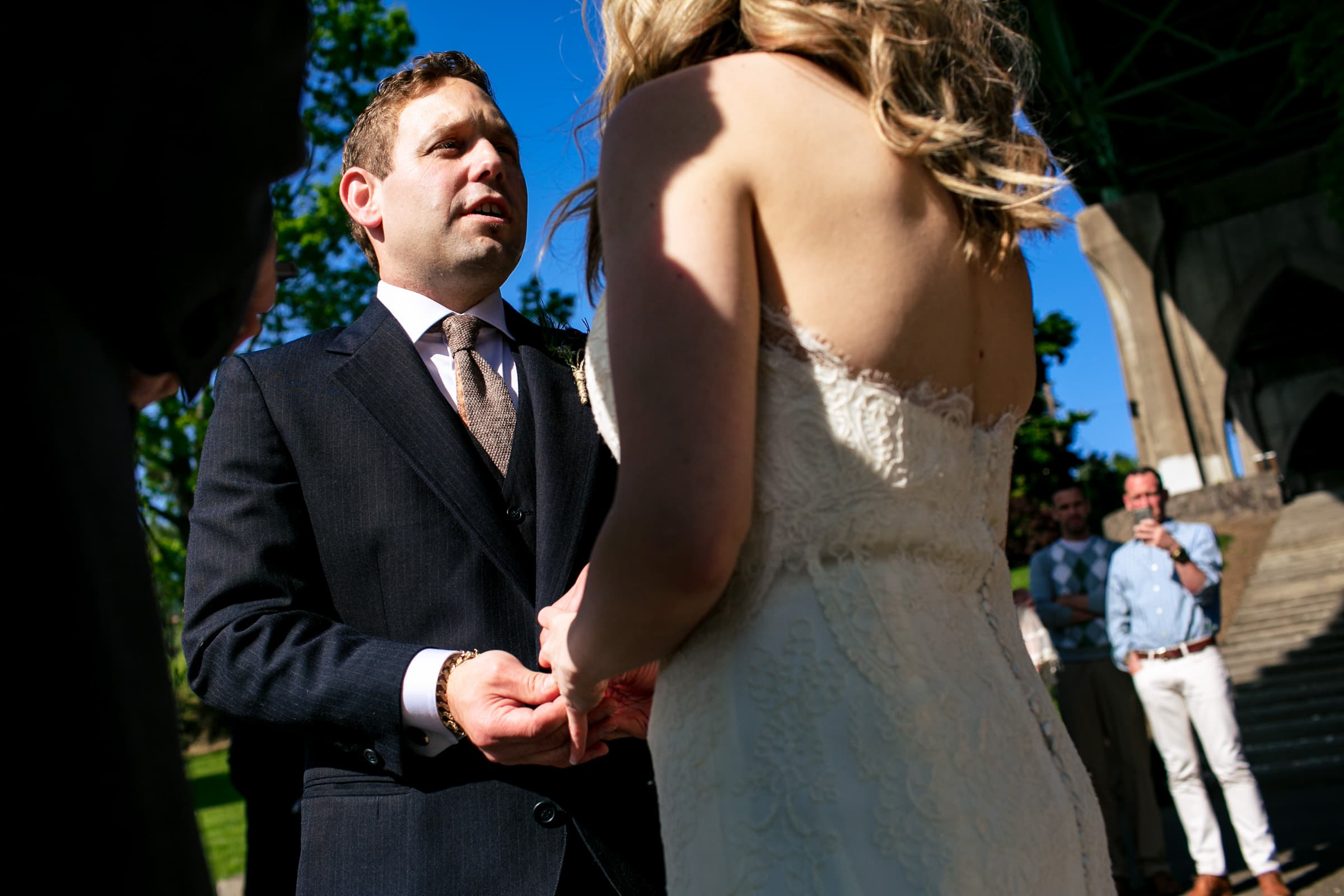 Groom exchanging vows during their outdoor small Cathedral Park Wedding ceremony in Portland Oregon