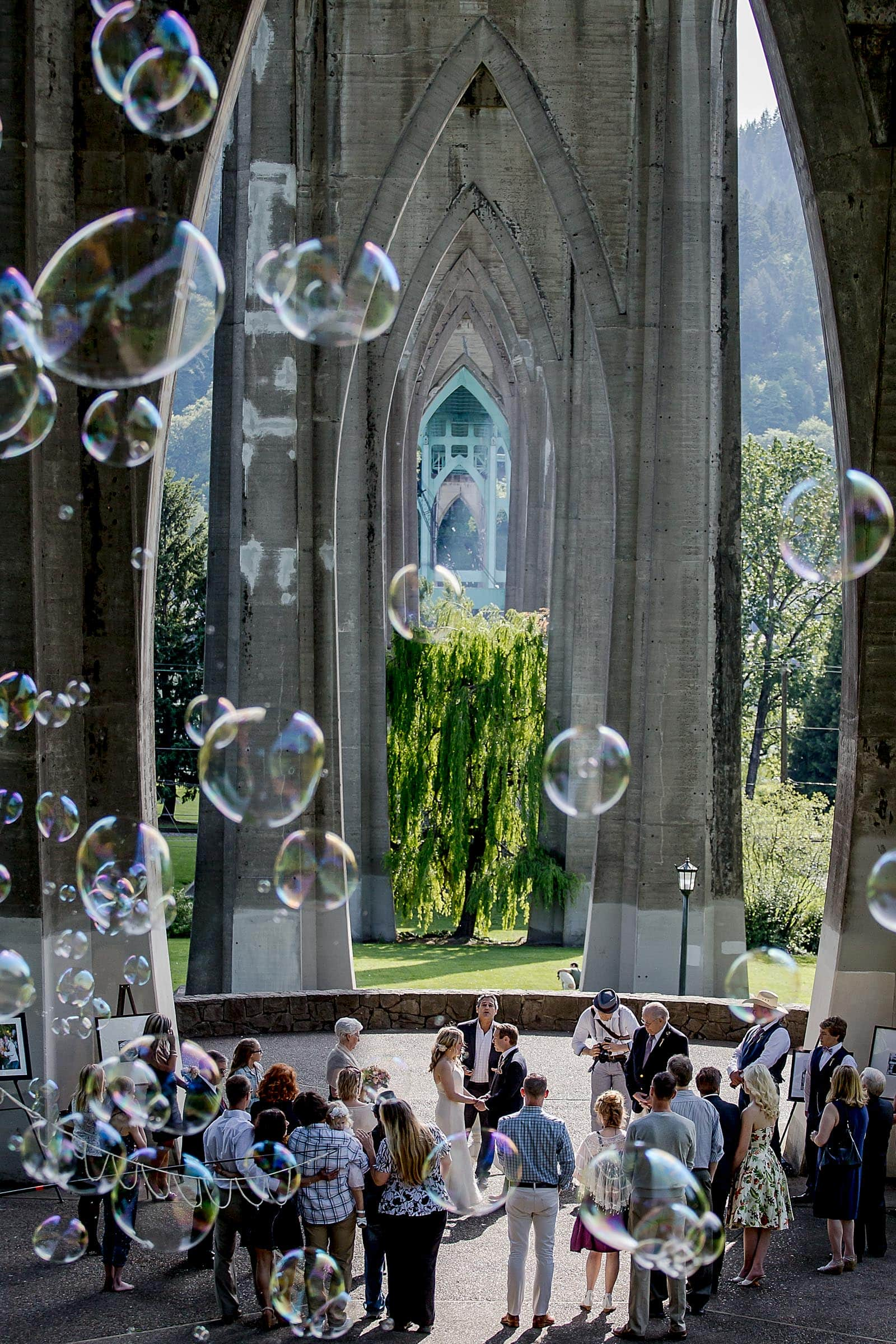 Wide angle perspective of the St Johns bridge during an outdoor small Cathedral Park Wedding ceremony in Portland Oregon
