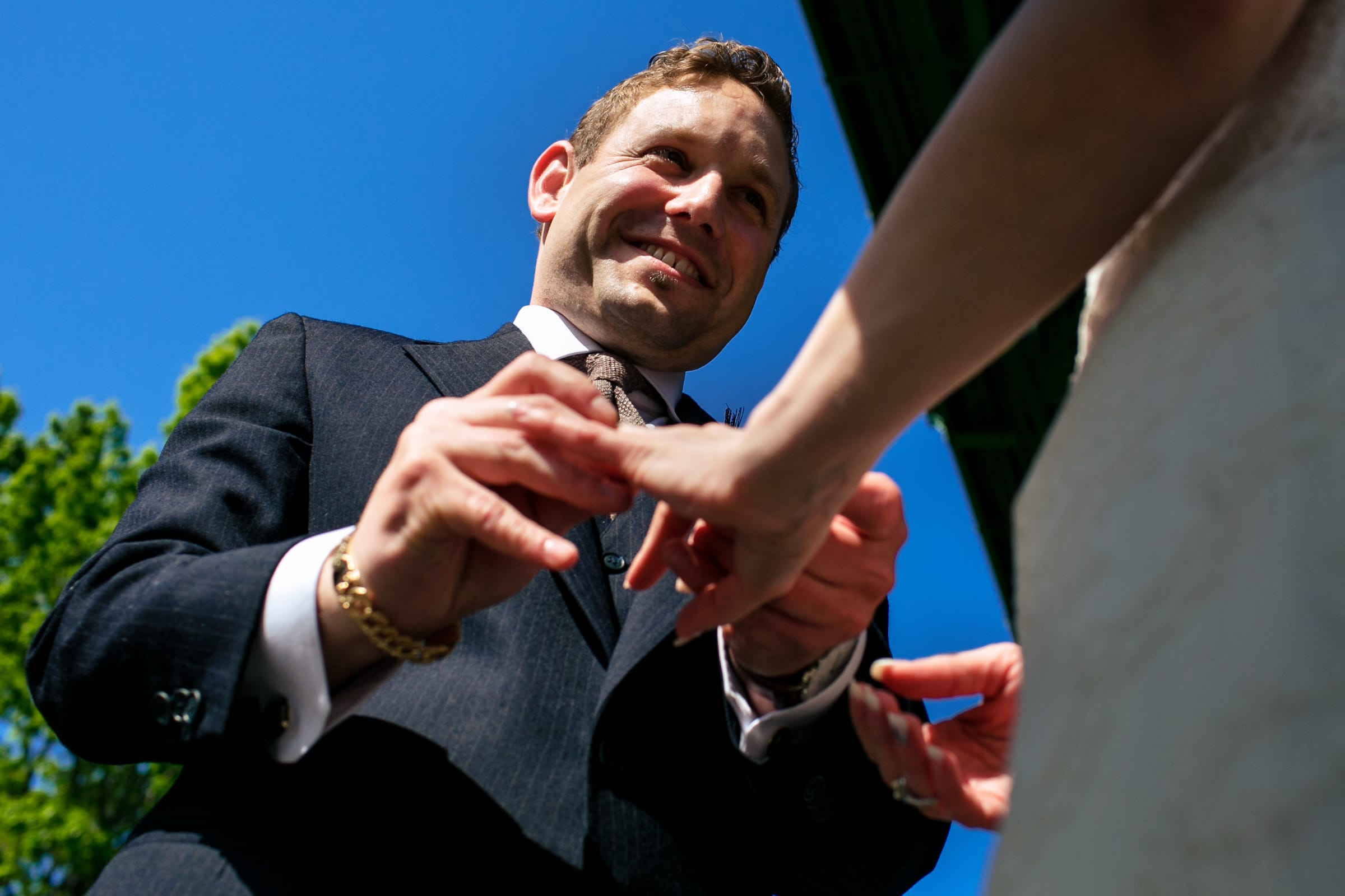 Groom putting on a ring for his bride during an outdoor small Cathedral Park Wedding ceremony in Portland Oregon