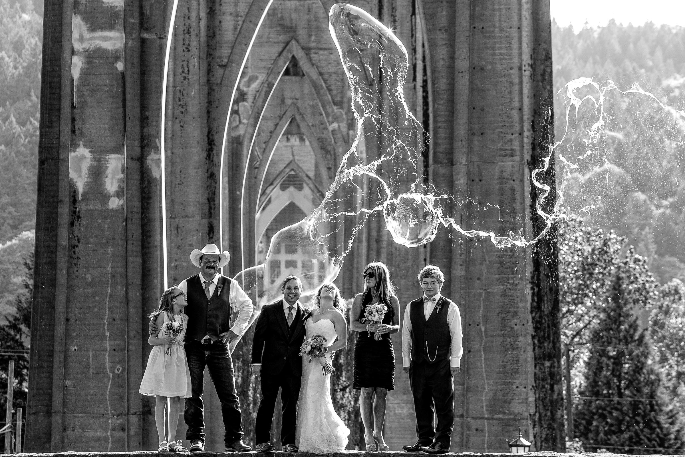 Huge bubbles exploding over bride and groom and family during their outdoor small Cathedral Park Wedding ceremony in Portland Oregon