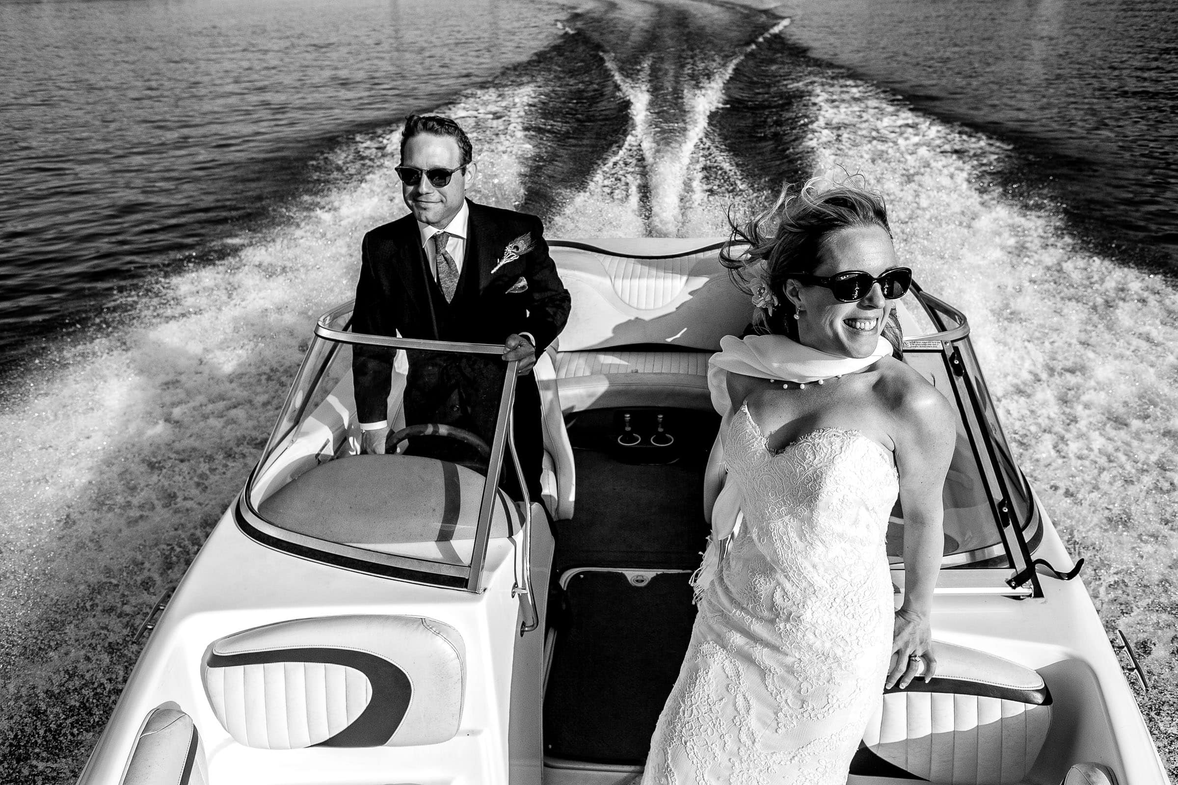 Bride and groom on a speed boat in the Willamette River following their outdoor small Cathedral Park Wedding ceremony in Portland Oregon