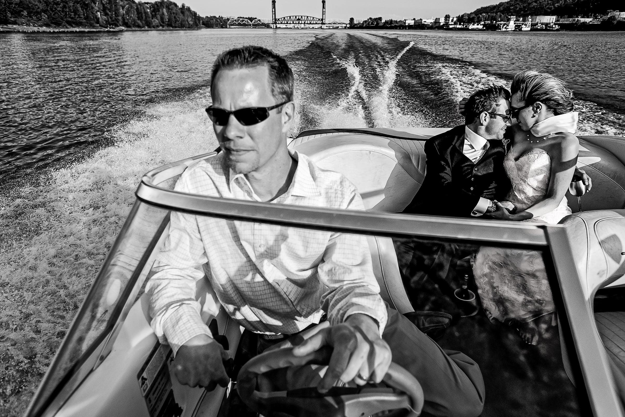 Photo of a bride and groom on the back of a speed boat with their friend driving moments after their outdoor small Cathedral Park Wedding ceremony in Portland Oregon