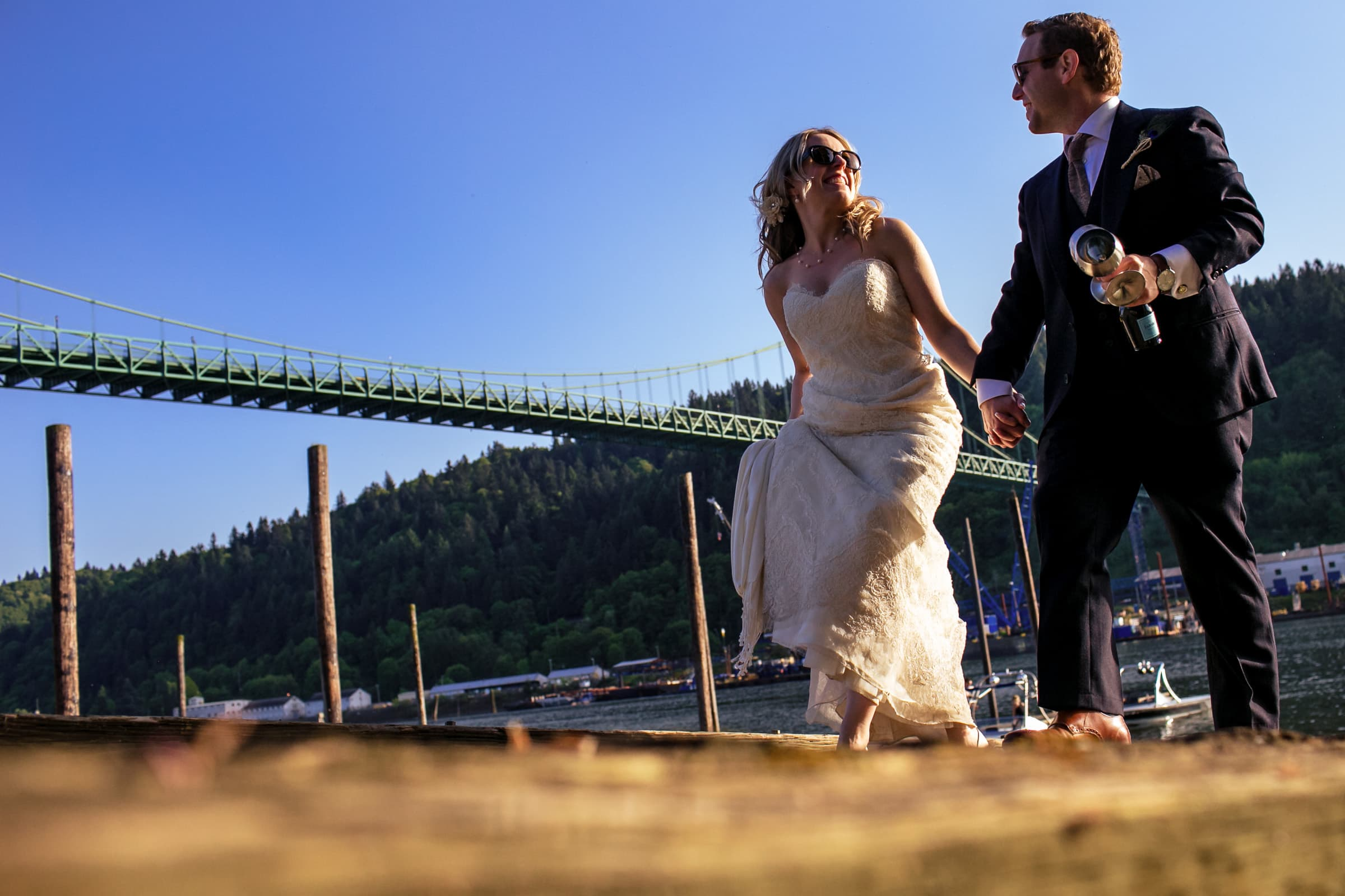 Bride and groom hiking up the hill after riding a speed boat down the Willamette River following their outdoor small Cathedral Park Wedding ceremony in Portland Oregon