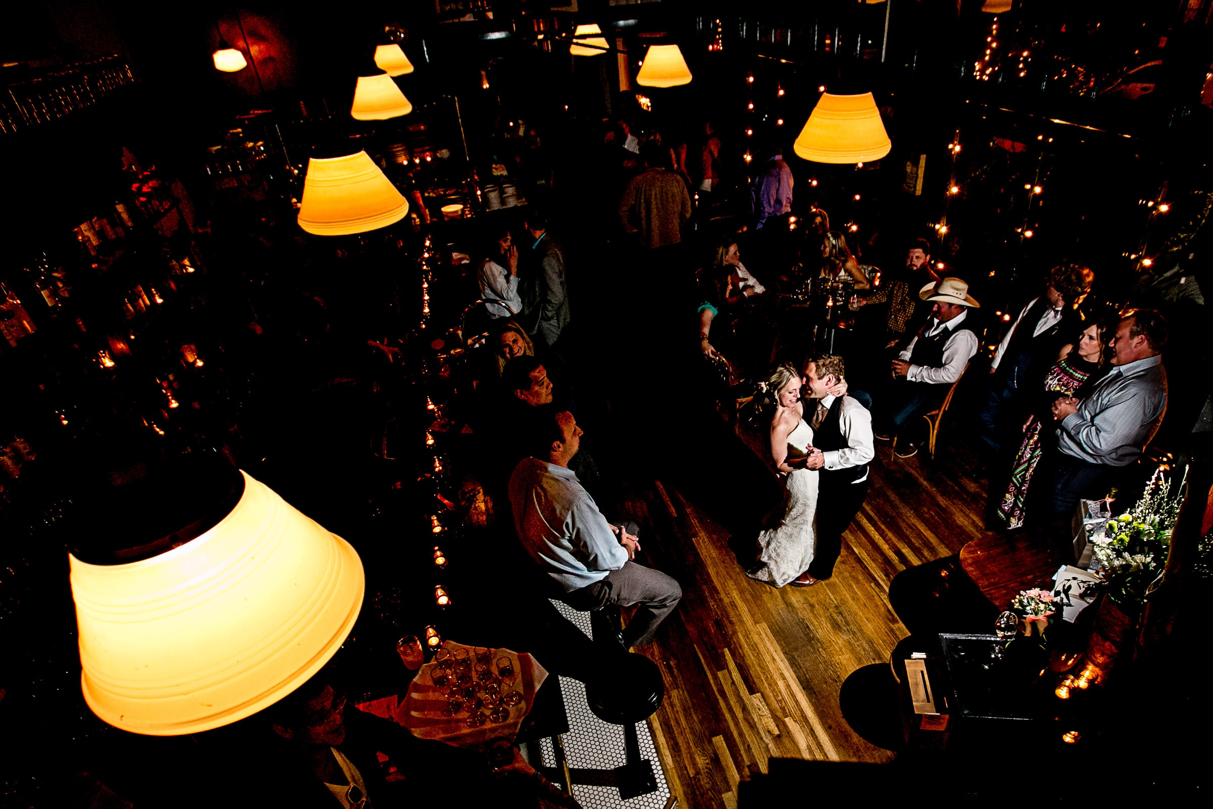 Wide angle photo of a bride and groom dancing in a bar at Besaws restaurant after their outdoor small Cathedral Park Wedding ceremony in Portland Oregon