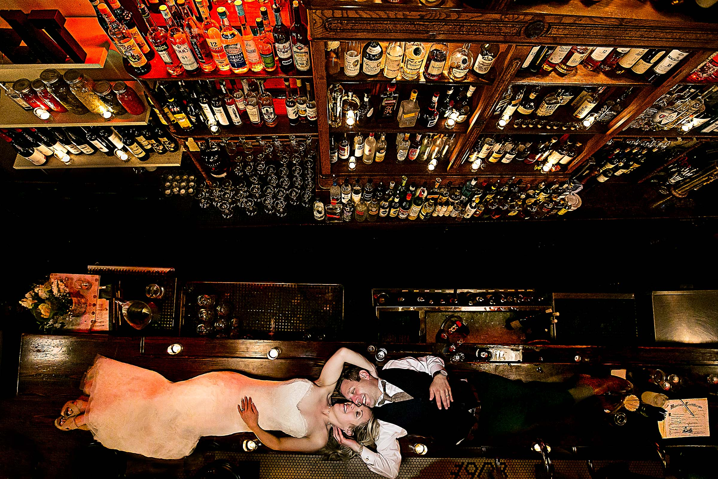 Bride and groom laying on the bar at Besaws restaurant after their outdoor small Cathedral Park Wedding ceremony in Portland Oregon
