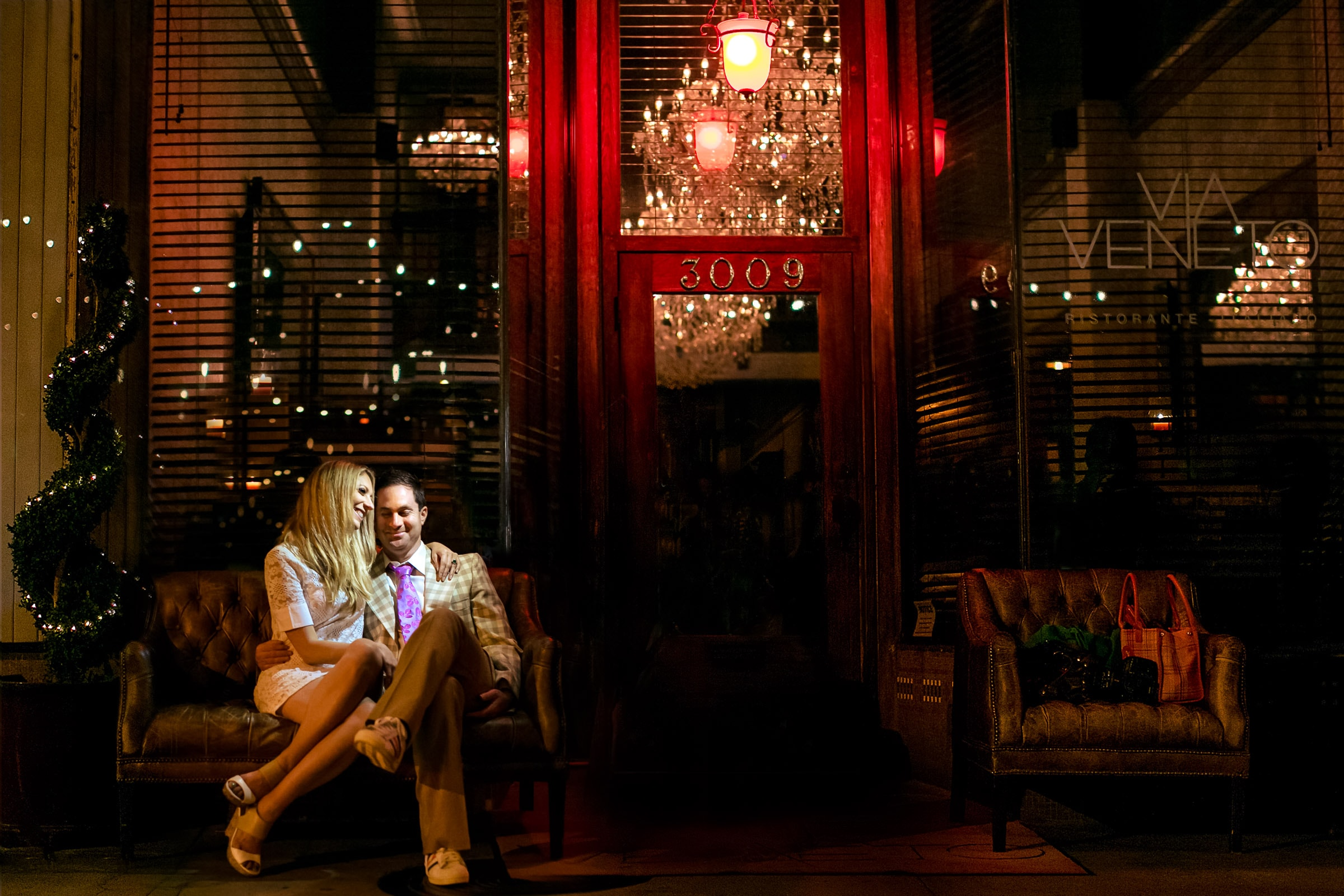 Los Angeles Engagement photo of a couple sitting outside Via Veneto. Photography by award winning wedding photographers Jos and Tree.