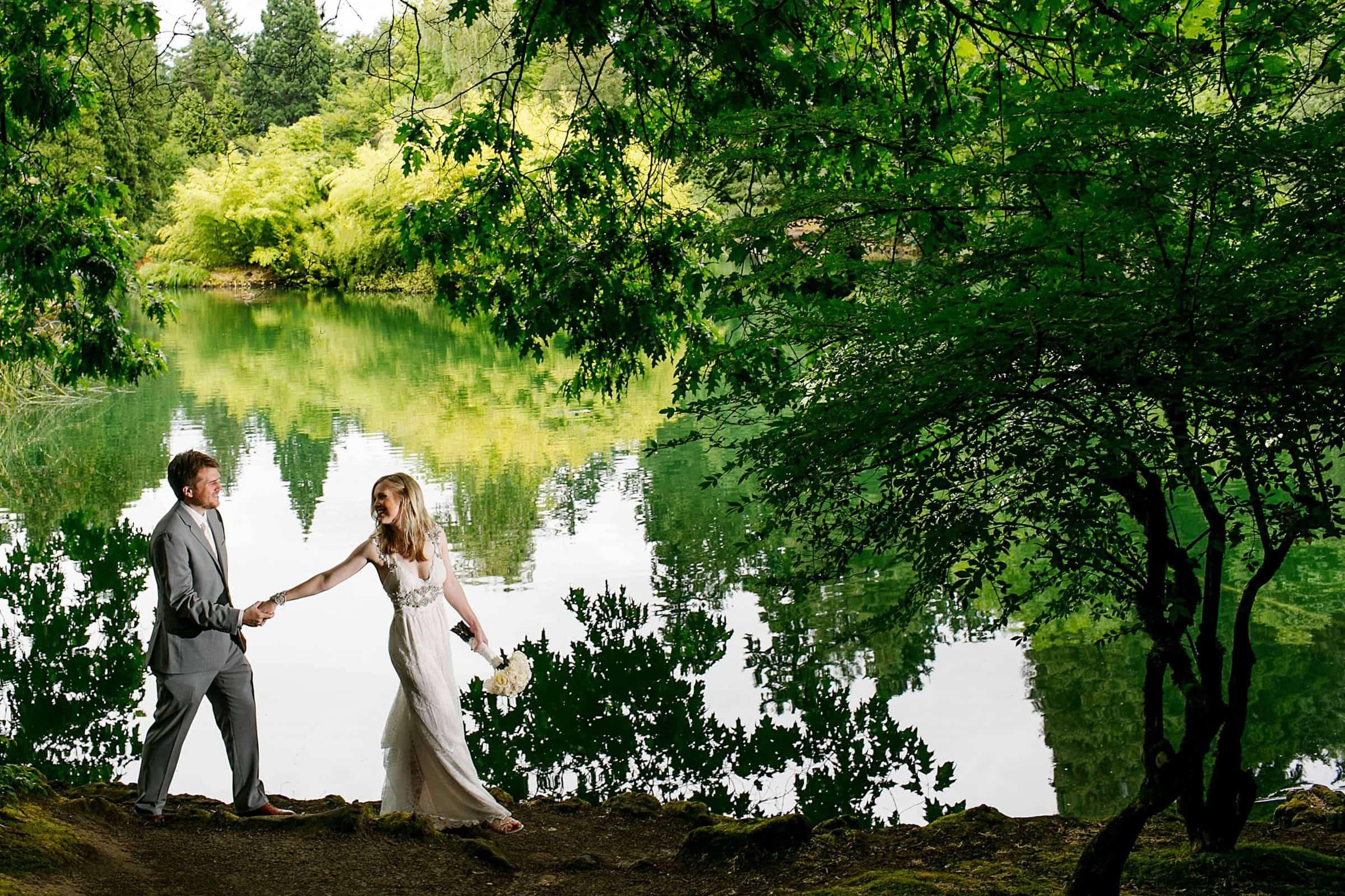 Bride and Groom walking along Laurelhurst Park in Portland near water