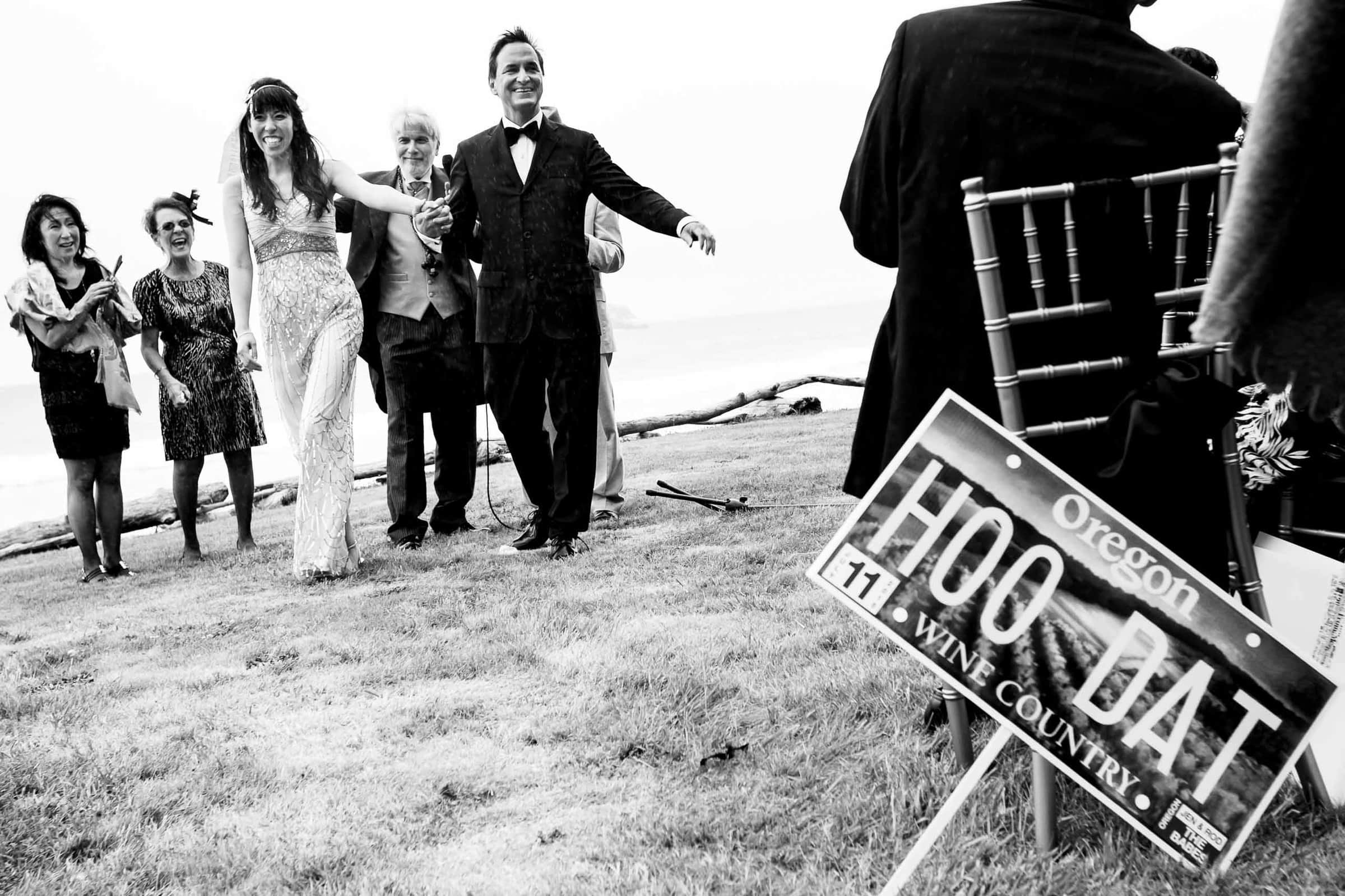 Bride and groom exiting their ceremony with New Orleans HOO DAT signs during their Manzanita elopement ceremony in Oregon