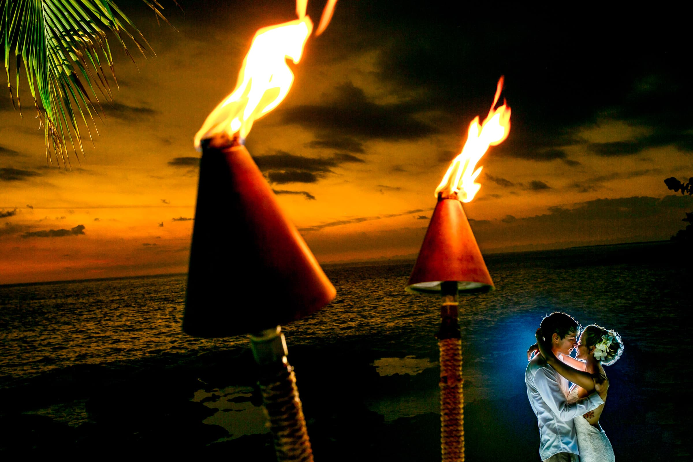 Bride and Groom at sunset with tiki torches during their Kailua Kona Wedding at the Kona Beach Bungalows on the Big Island of Hawaii
