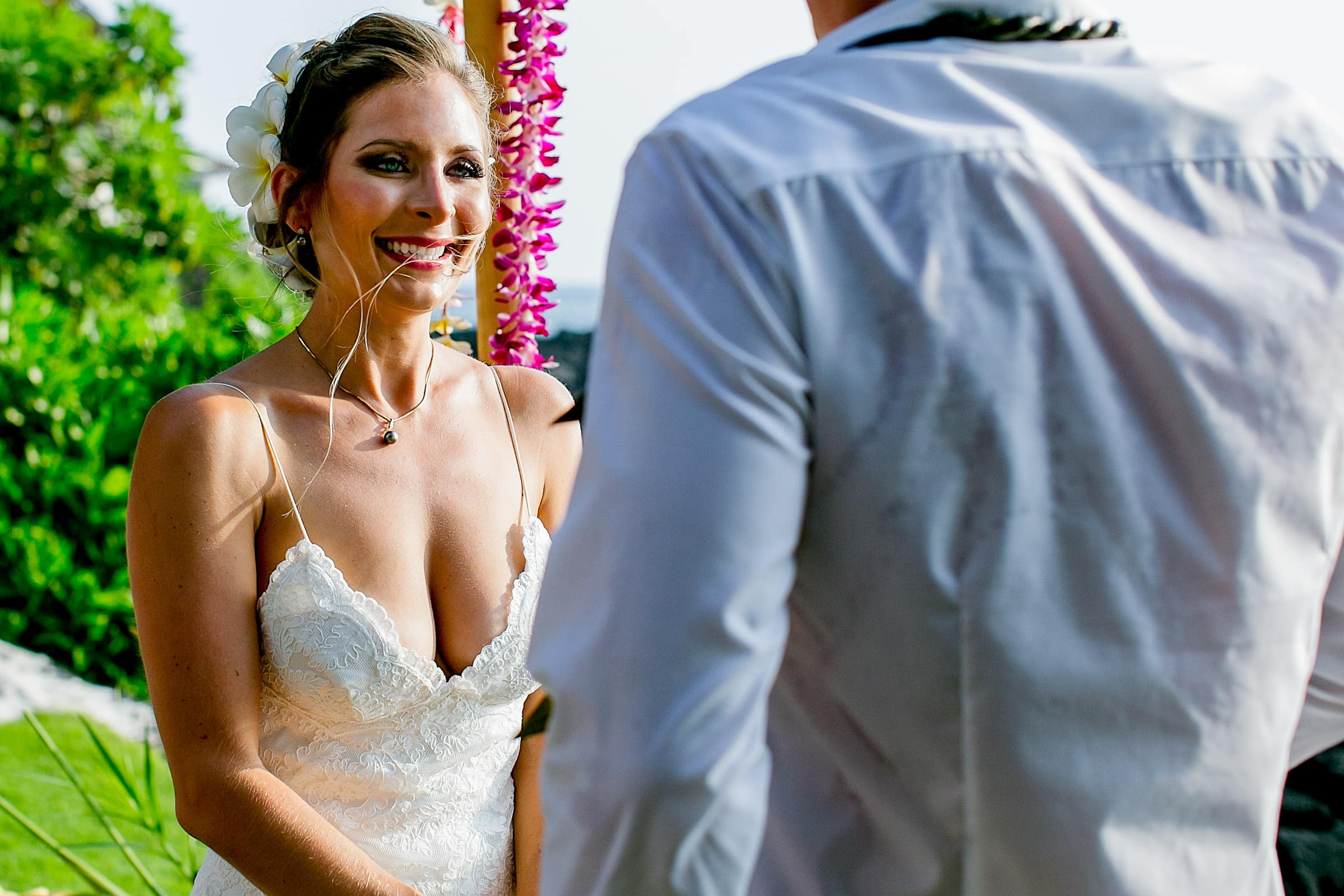 Bride smile toward her groom during a Kailua Kona Wedding ceremony at the Kona Beach Bungalows on the Big Island of Hawaii
