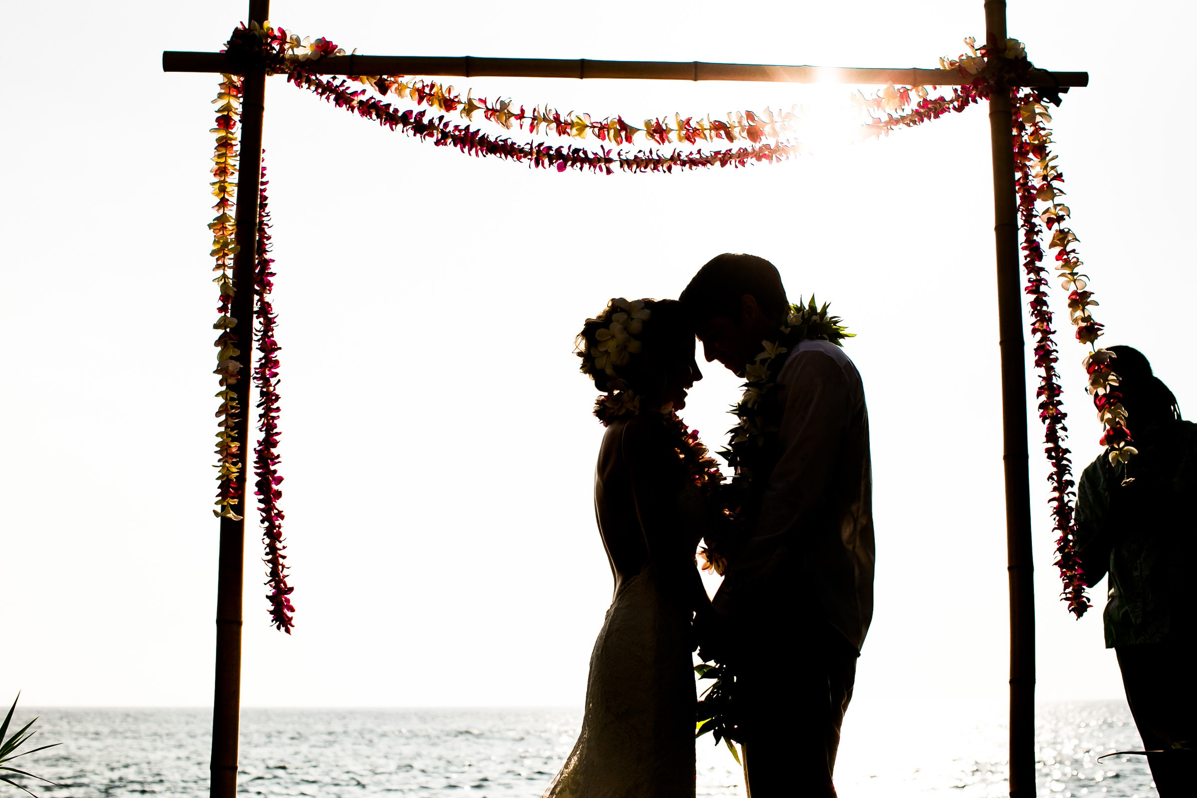 Bride and groom embracing in a silhouette during a Kailua Kona Wedding ceremony at the Kona Beach Bungalows on the Big Island of Hawaii