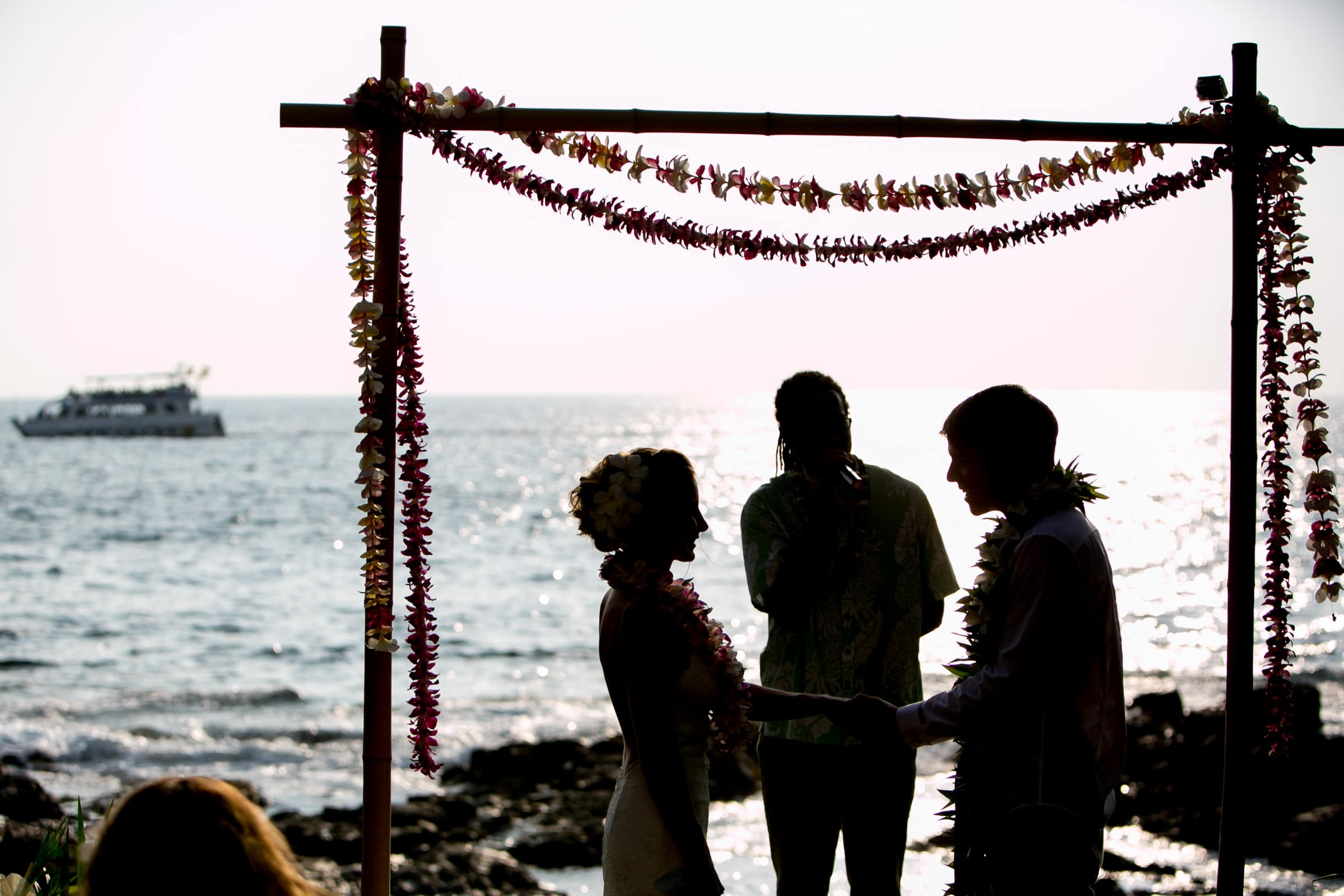Bride and groom exchanging vows in a silhouette during a Kailua Kona Wedding ceremony at the Kona Beach Bungalows on the Big Island of Hawaii