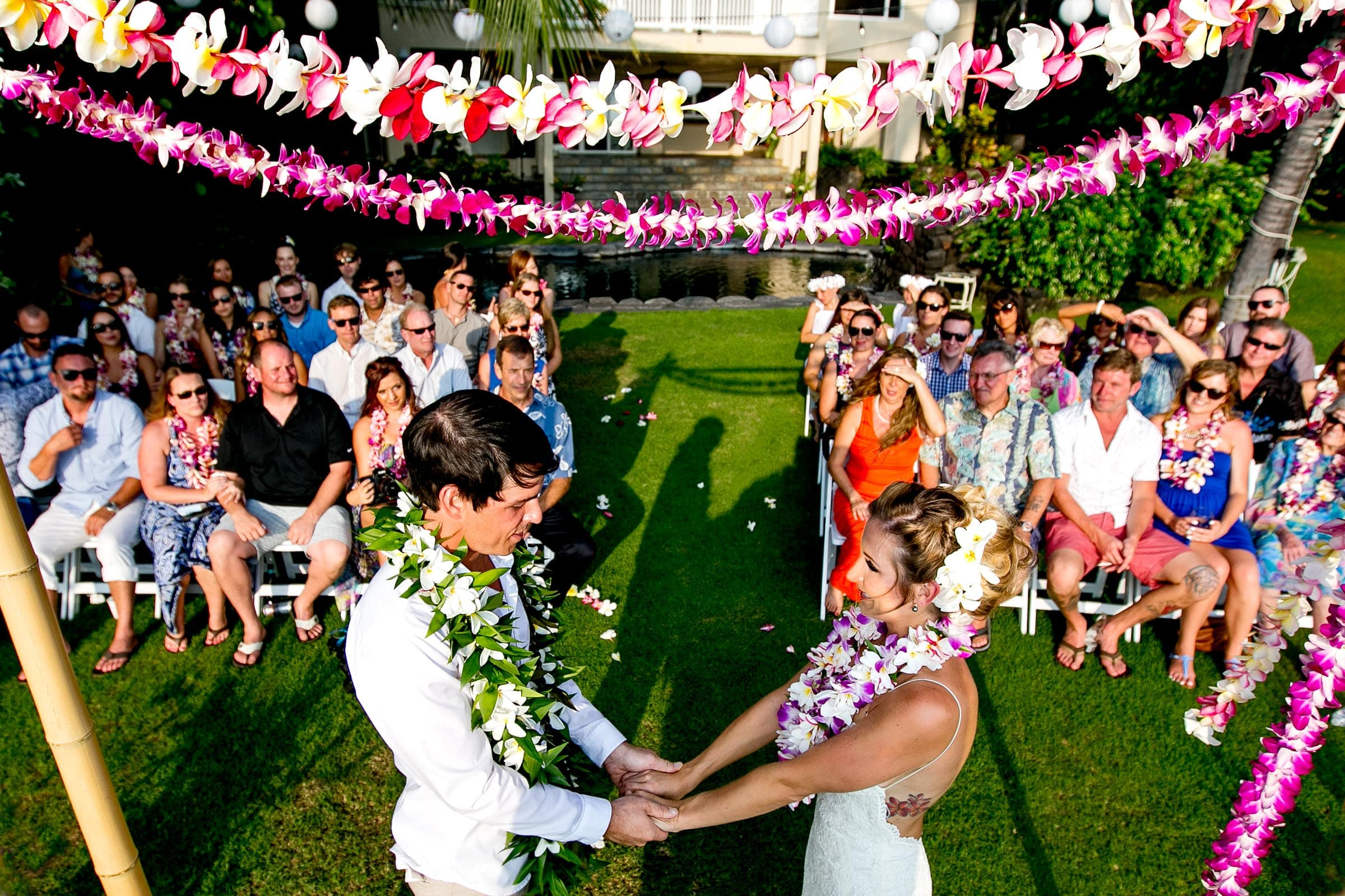 Wide angle view of guests through the bride and groom during a Kailua Kona Wedding ceremony at the Kona Beach Bungalows on the Big Island of Hawaii