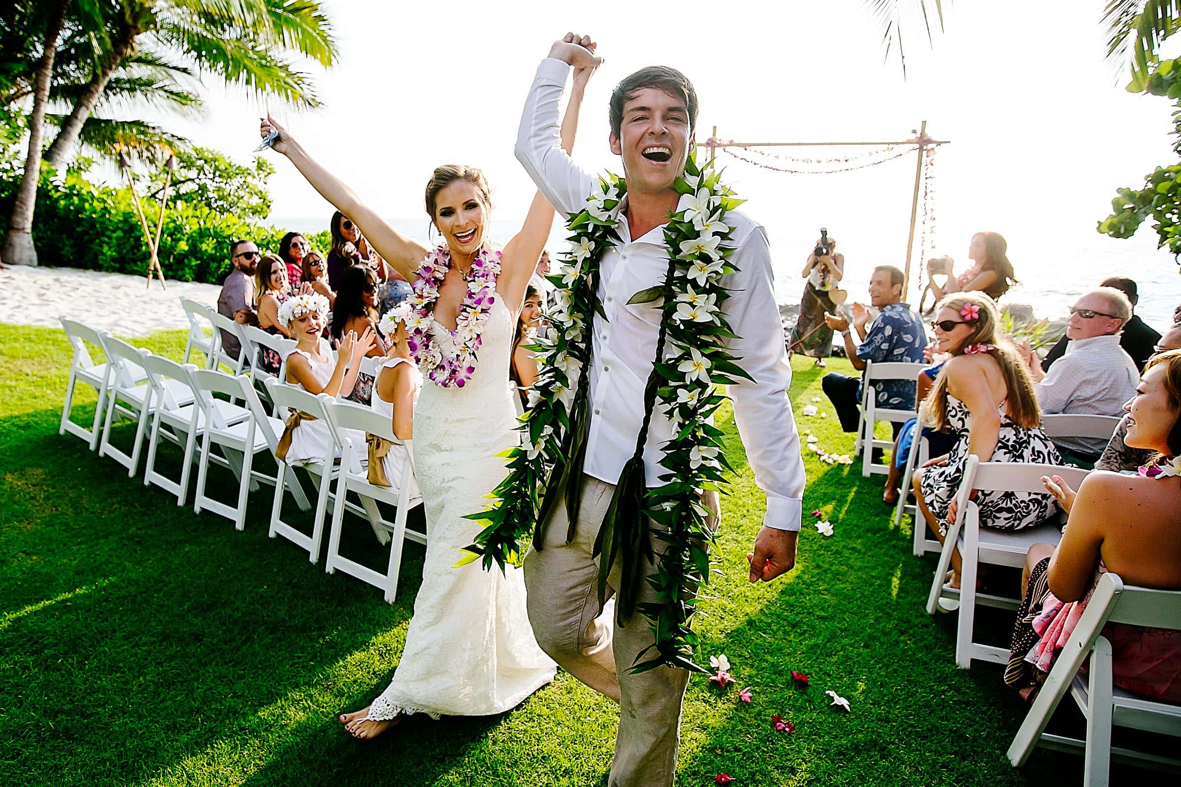 Bride and groom celebrating their exit during a Kailua Kona Wedding ceremony at the Kona Beach Bungalows on the Big Island of Hawaii