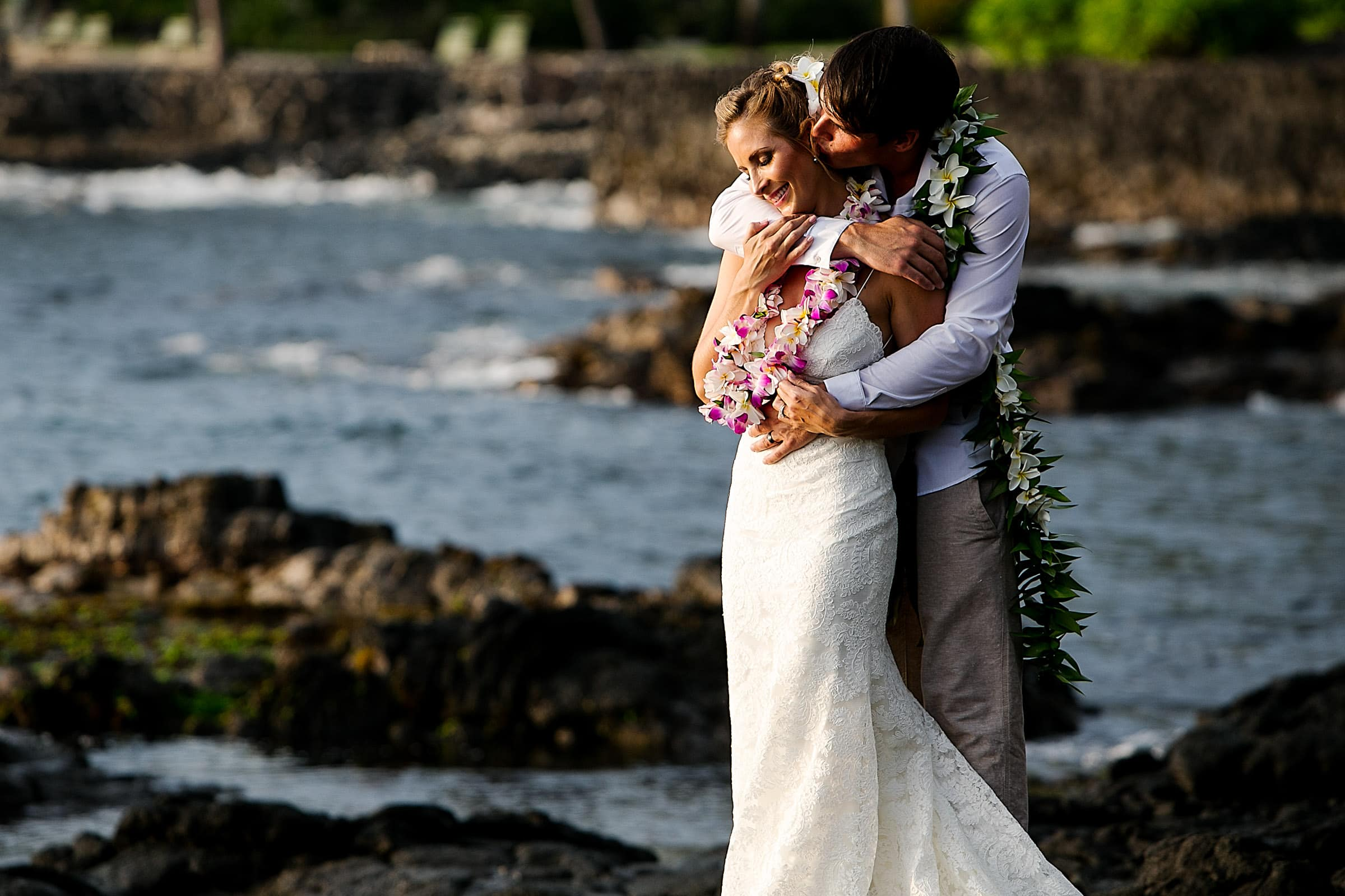 Bride and groom embracing near the ocean during their Kailua Kona Wedding at the Kona Beach Bungalows on the Big Island of Hawaii
