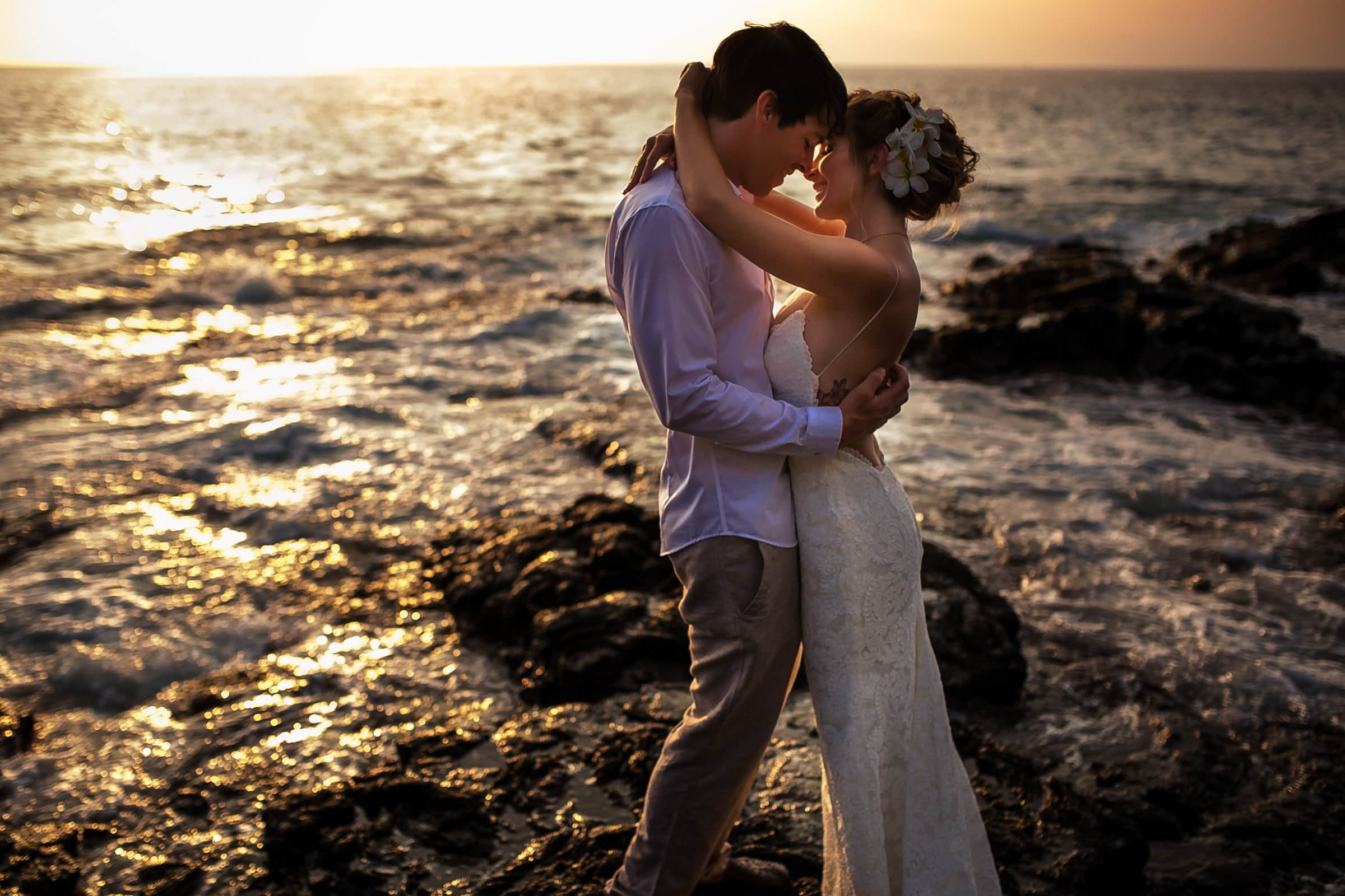 Bride and groom embracing near the ocean during a warm lit sunset during their Kailua Kona Wedding at the Kona Beach Bungalows on the Big Island of Hawaii