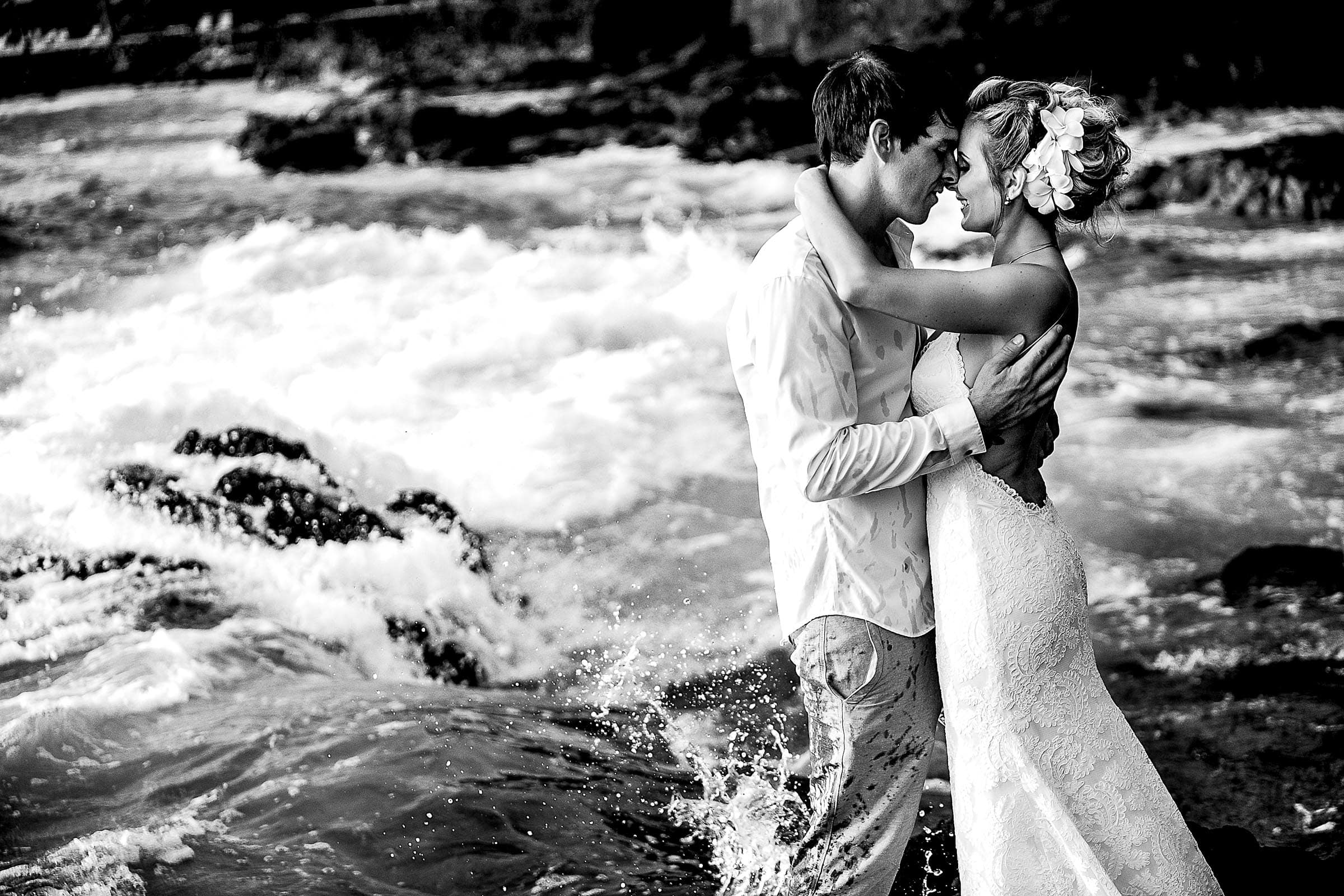 Black and white photo of a bride and groom embracing near the ocean during their Kailua Kona Wedding at the Kona Beach Bungalows on the Big Island of Hawaii