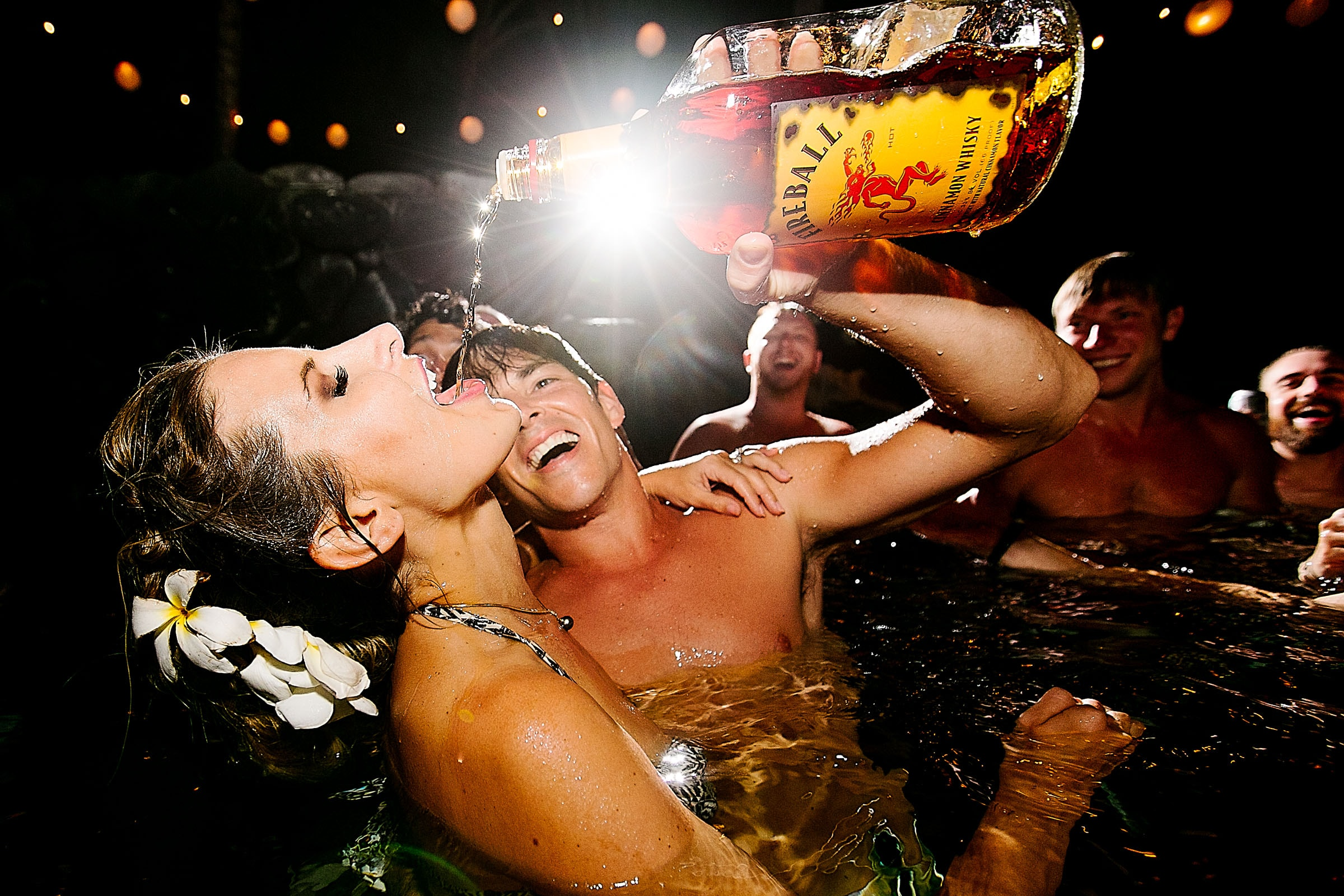 Bride having tequila poured into her mouth during a Kailua Kona Wedding at the Kona Beach Bungalows on the Big Island of Hawaii