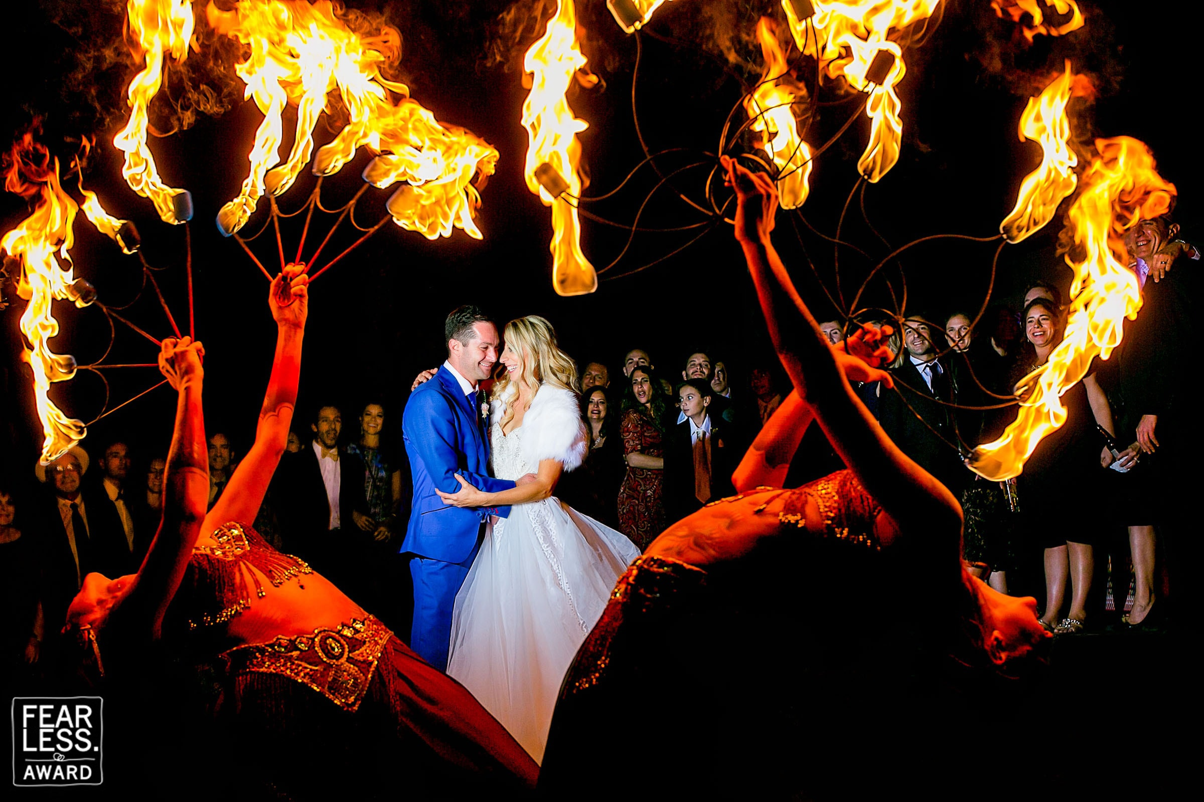 Creative portrait of Courtney White and Brian Procel fearless photographers award winning photo with circus flames surrounding them in the shape of a heart during their Merv Griffin Estate Wedding in Palm Springs