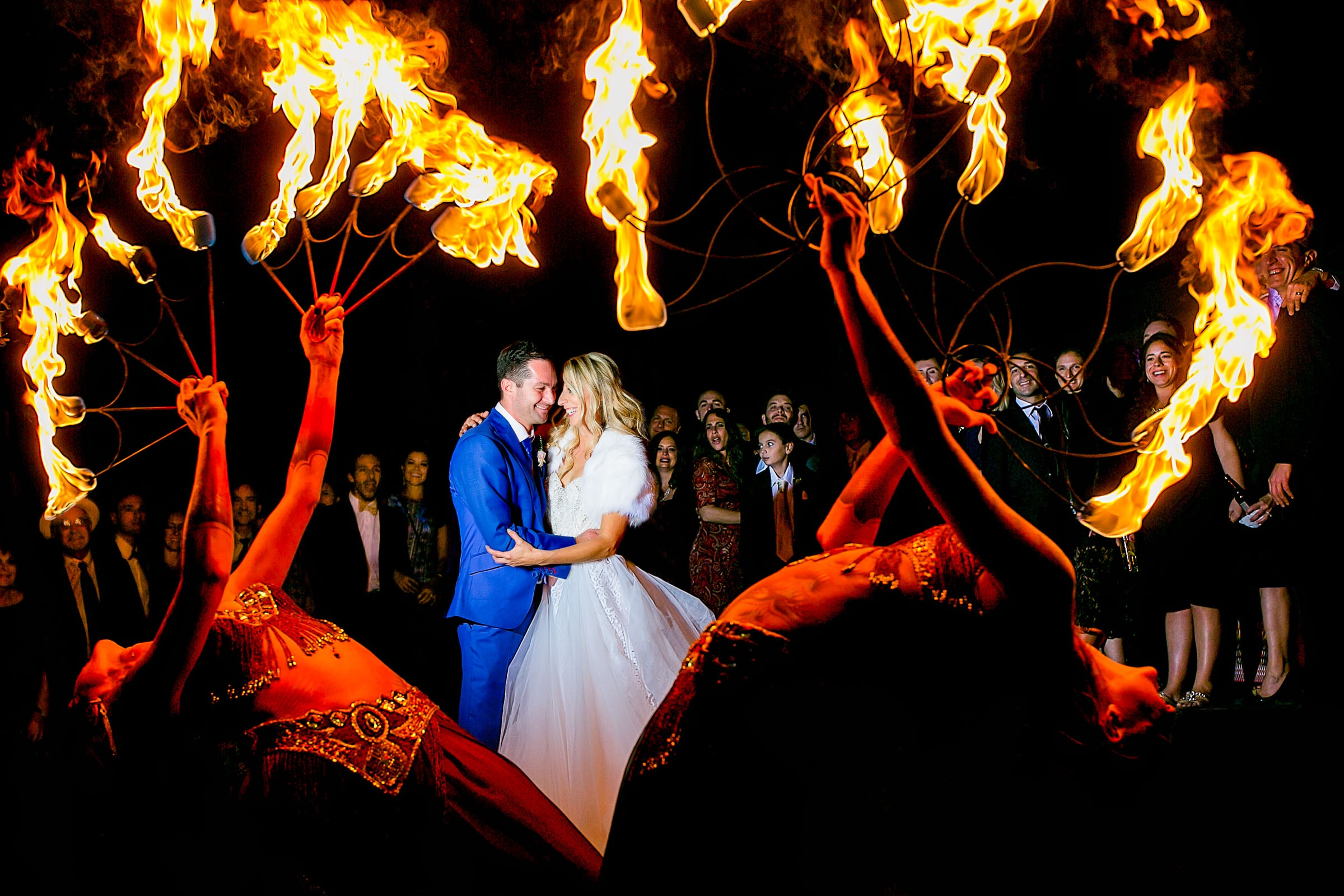 Creative portrait of bride and groom surrounded by flames thrown by circus performers during their Merv Griffin Estate Wedding in Palm Springs