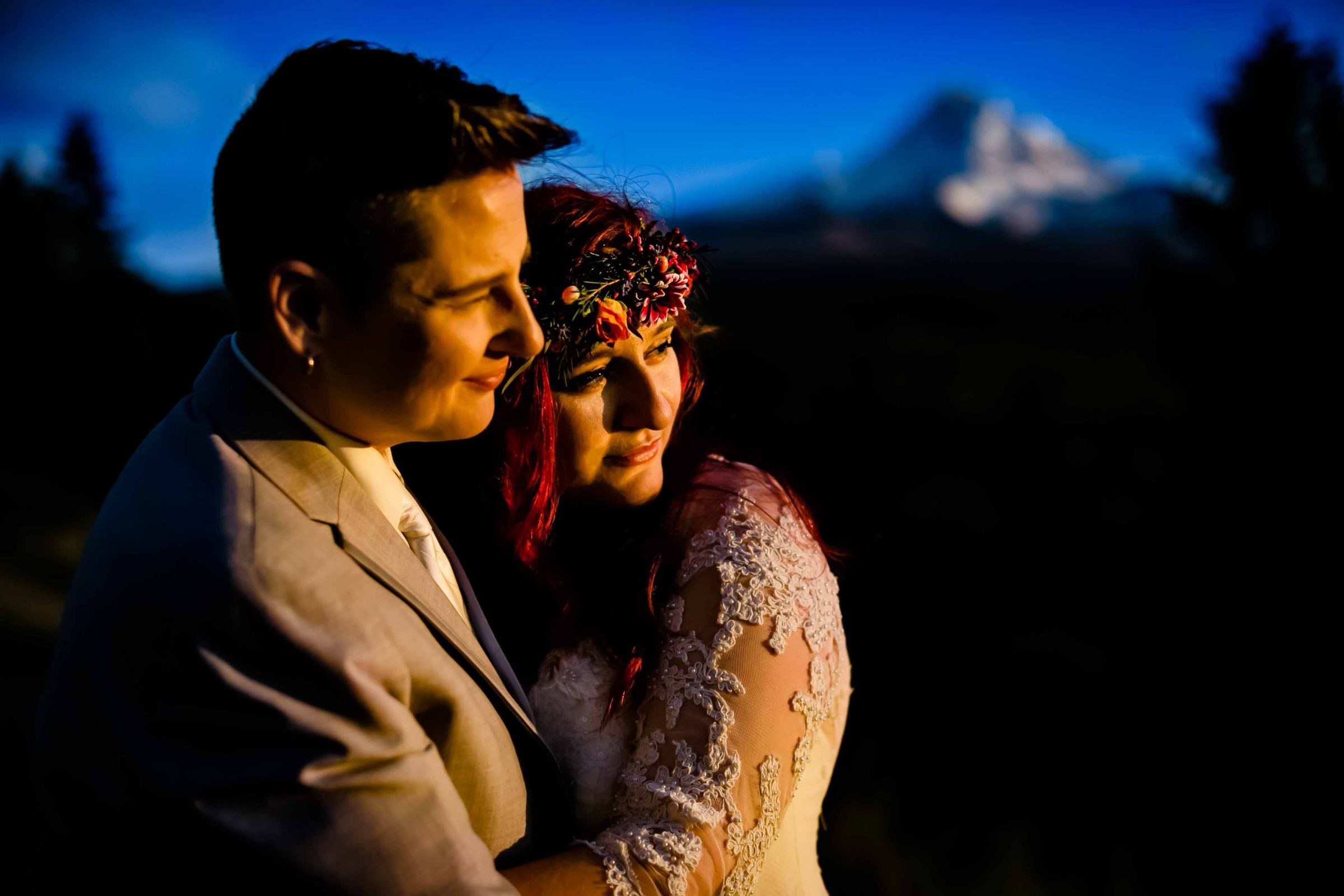 A bride and bride with dramatic sunlight on their faces during a Mt Hood Organic Farms wedding at sunset