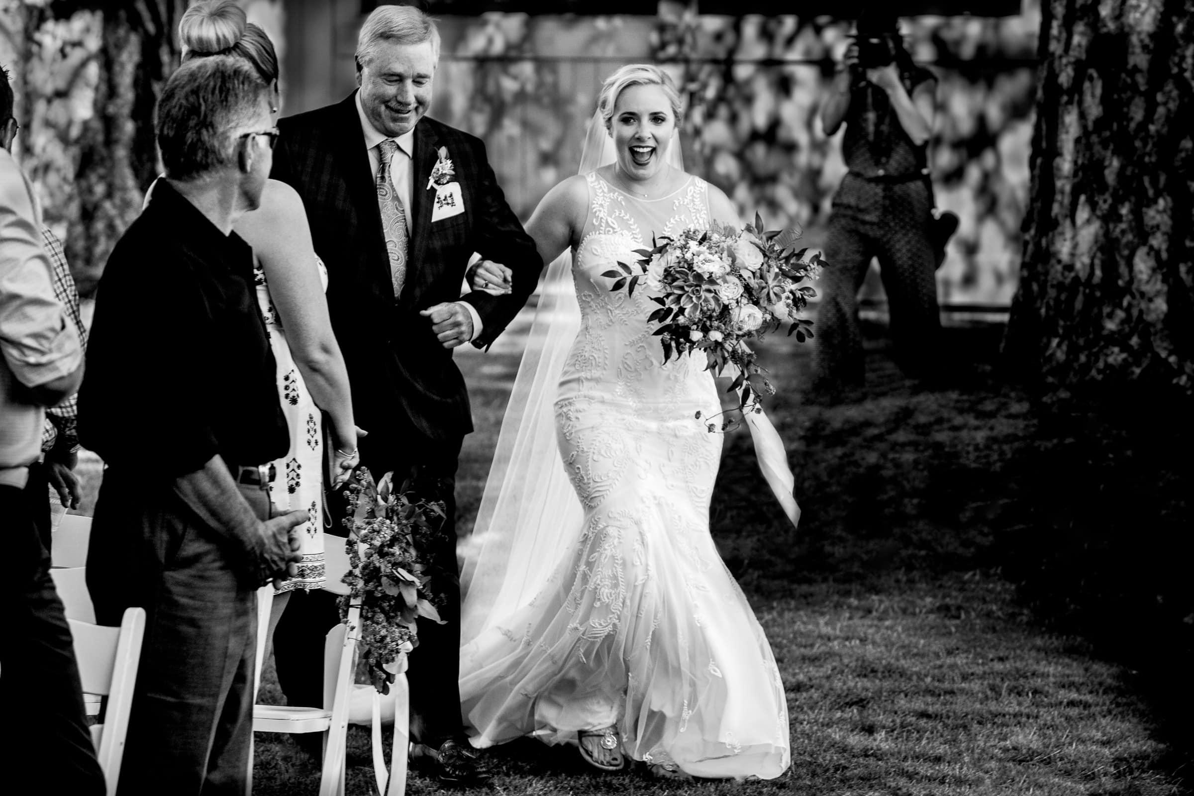 Happy bride walking into Black Butte Ranch wedding ceremony in Central Oregon