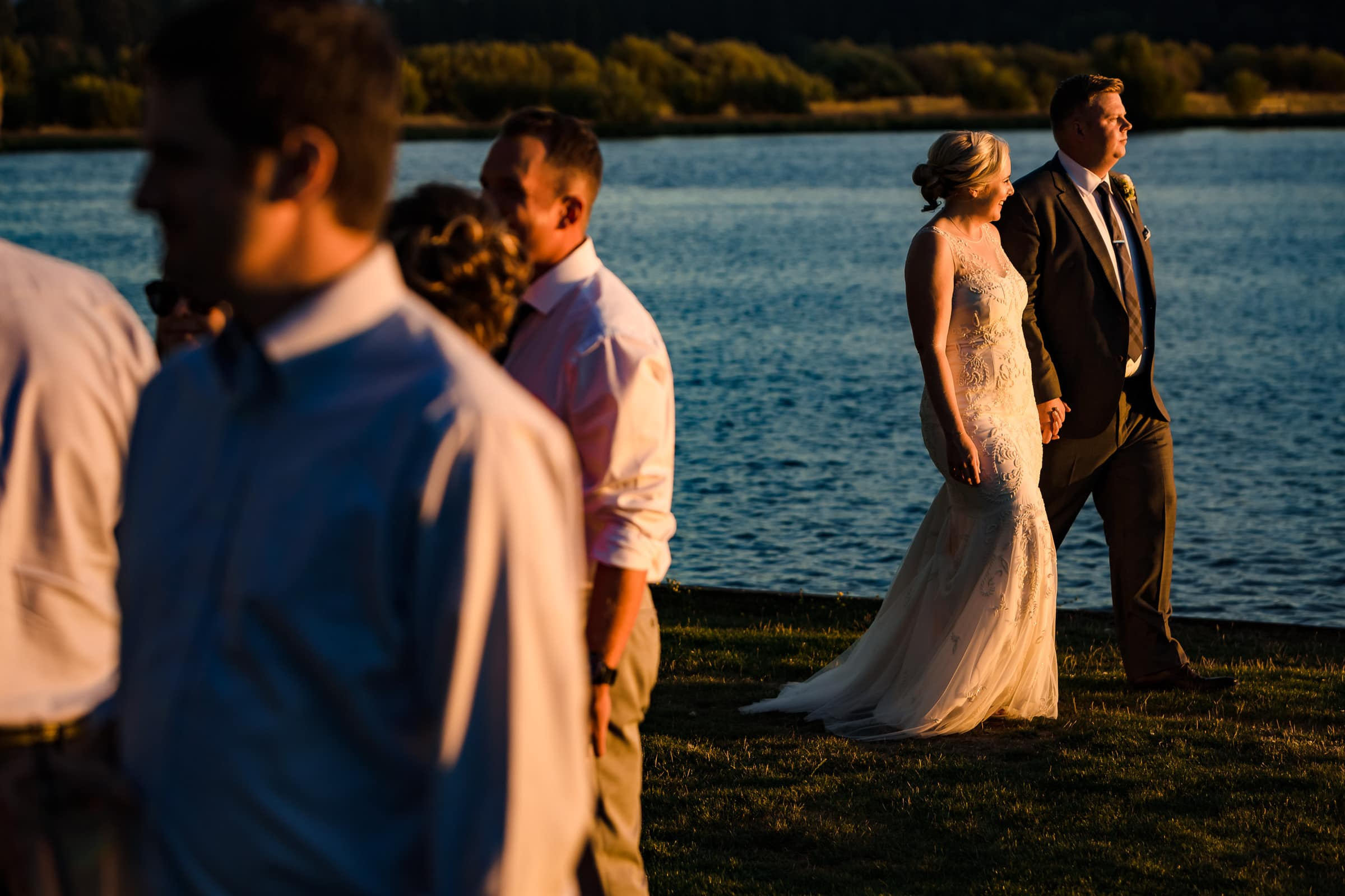 Bride and groom walking near the water at sunset at their Black Butte Ranch wedding in Central Oregon