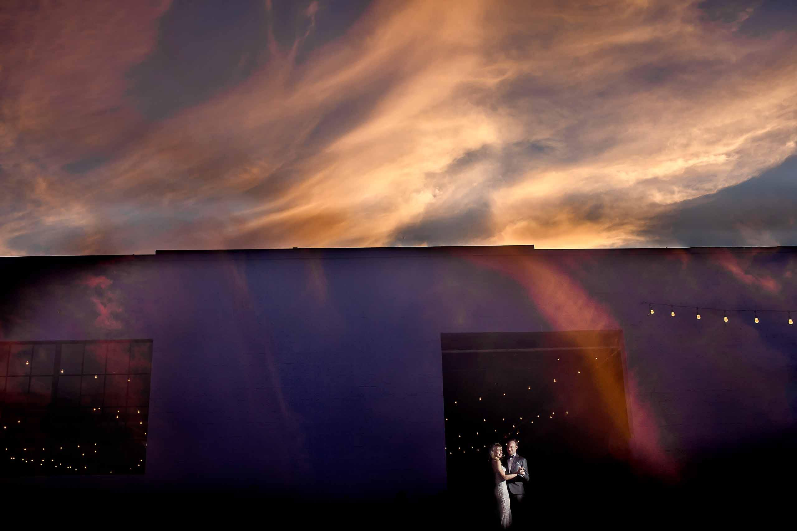 Creative portrait of bride and groom dancing during their Castaway Portland wedding reception with sun flares