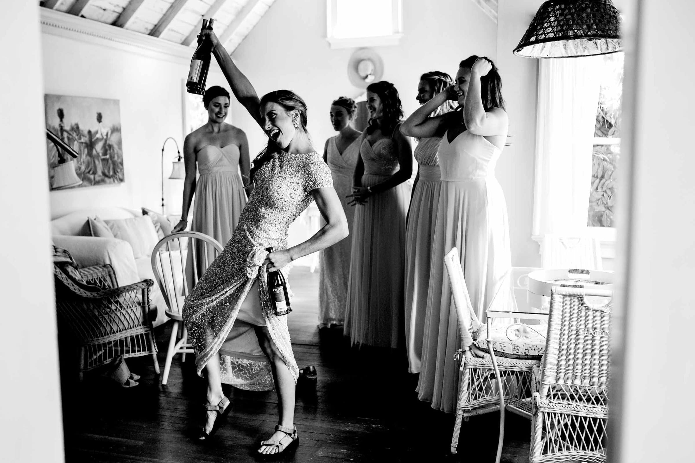 Fun photo of a bridesmaid with champagne in two hands while getting ready for a Mt Hood Organic Farms wedding near Hood River Oregon