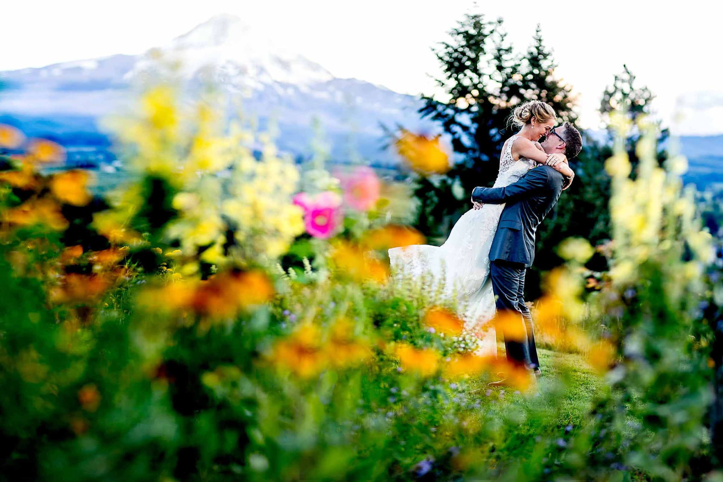 Bride and groom hugging in flowers at sunset during their Mt Hood Organic Farms wedding near Hood River Oregon