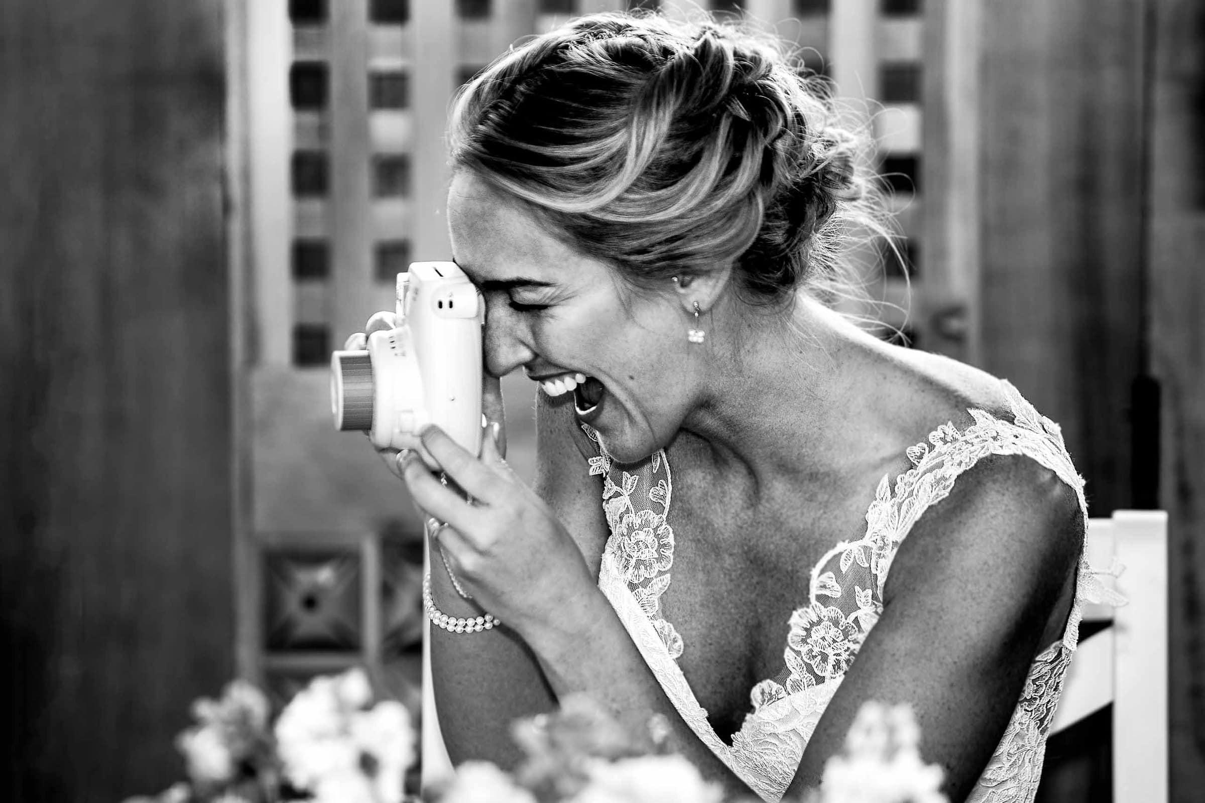 Fun photo of bride taking polaroid photos during her Mt Hood Organic Farms wedding reception near Hood River Oregon