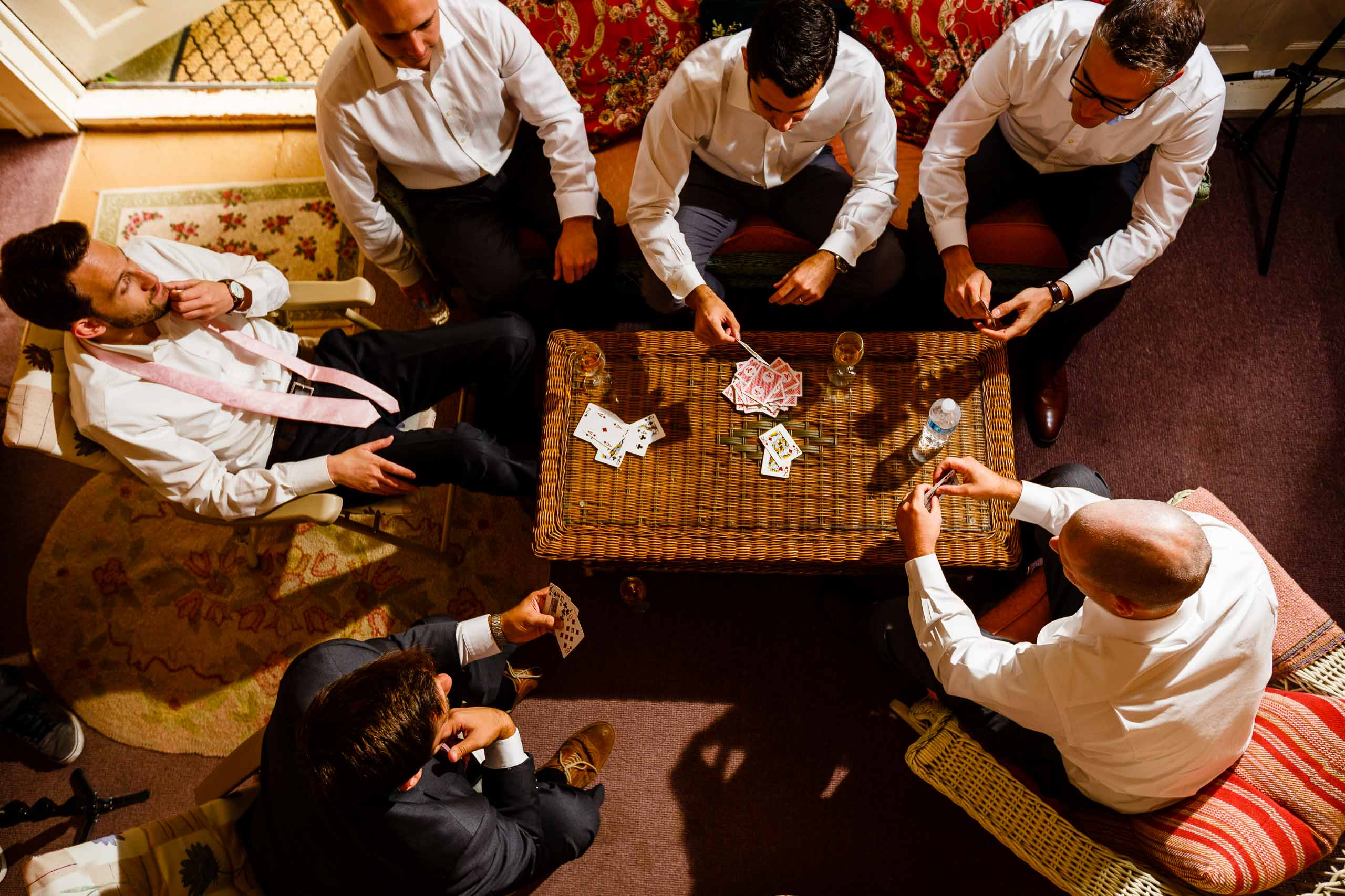 Groomsmen playing cards while getting ready for a Mt Hood Organic Farms wedding outside Hood River Oregon