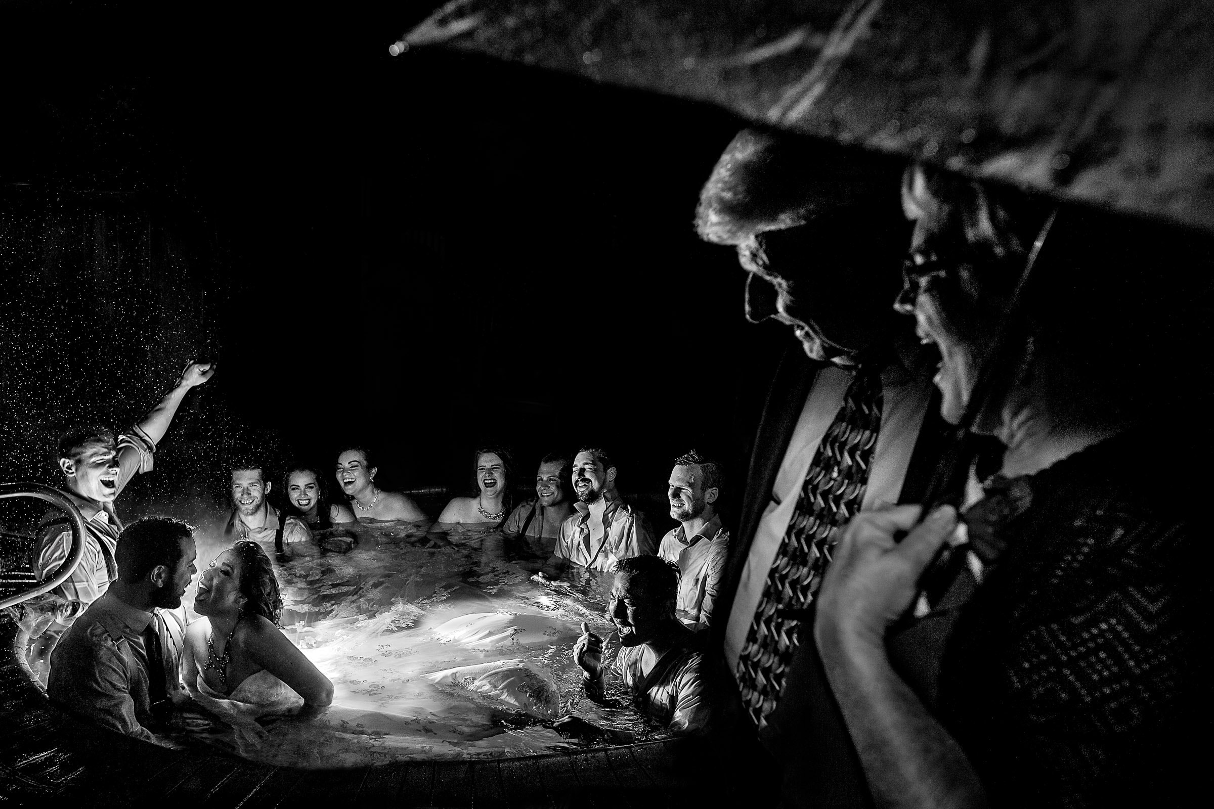 And award winning wedding photo by The Worlds Best Wedding Photos contest of bride and groom in a hot tub with family and friends at a Resort at the Mountain Wedding in Oregon near Mt Hood