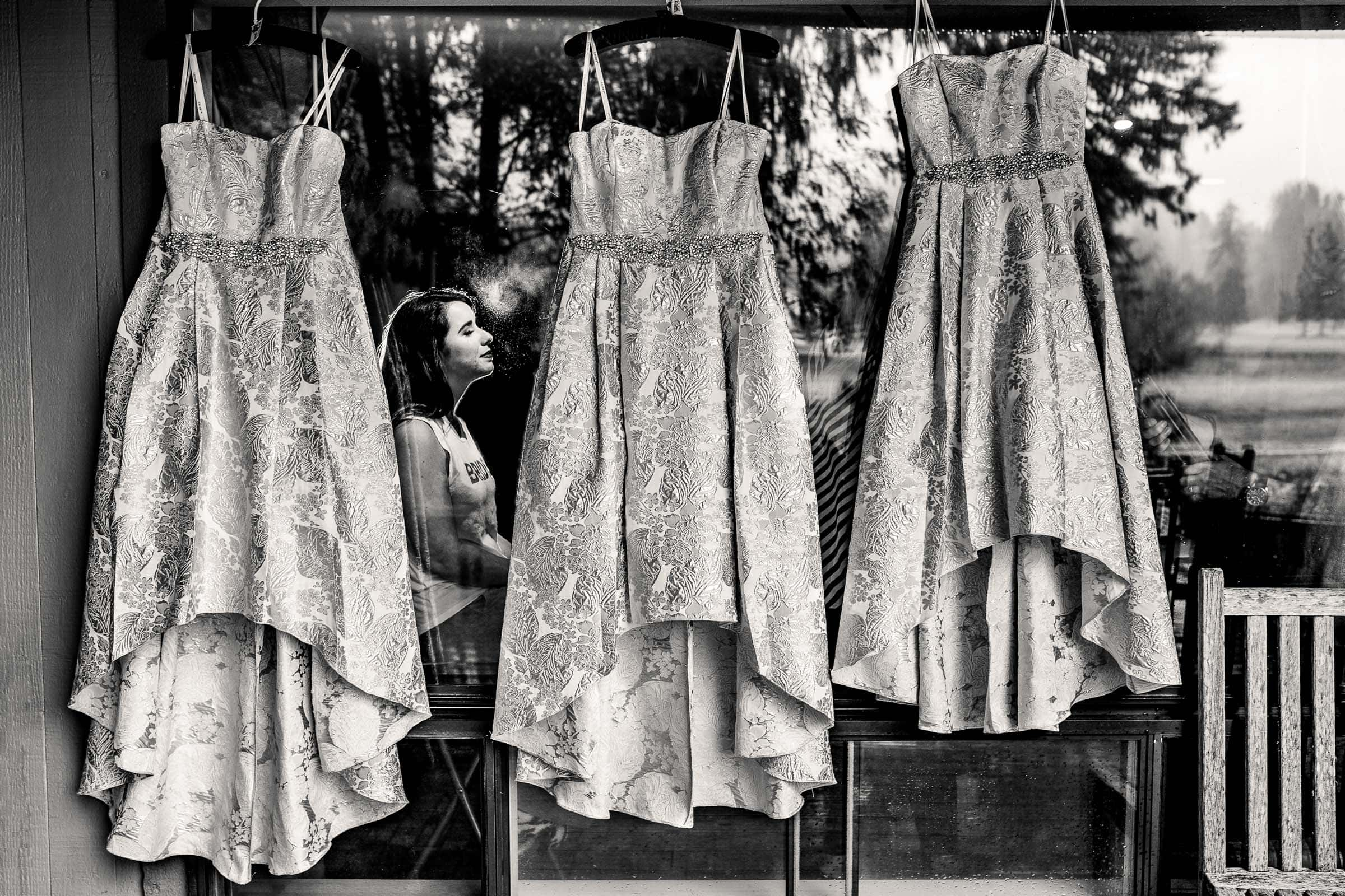 Bride getting ready with dresses and reflection at her Resort at the Mountain wedding in Oregon near Mt Hood.