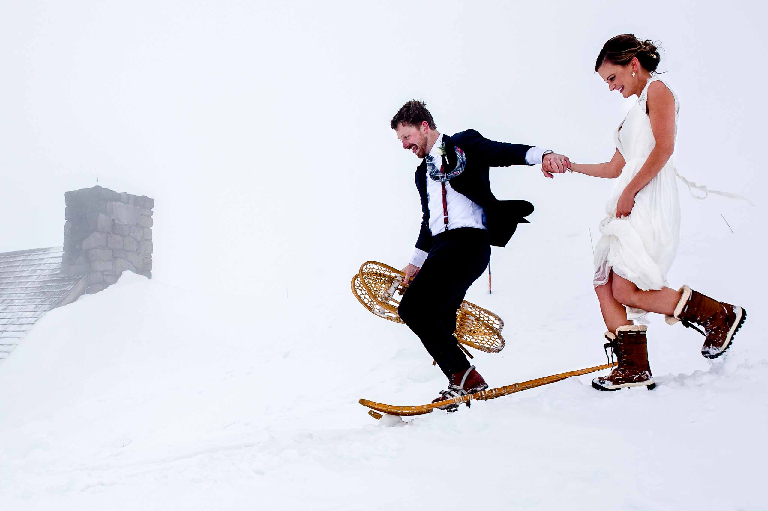 Bride and Groom running in snow shoes atop Mt Hood above Timberline Lodge at Silcox Hut for their intimate wedding