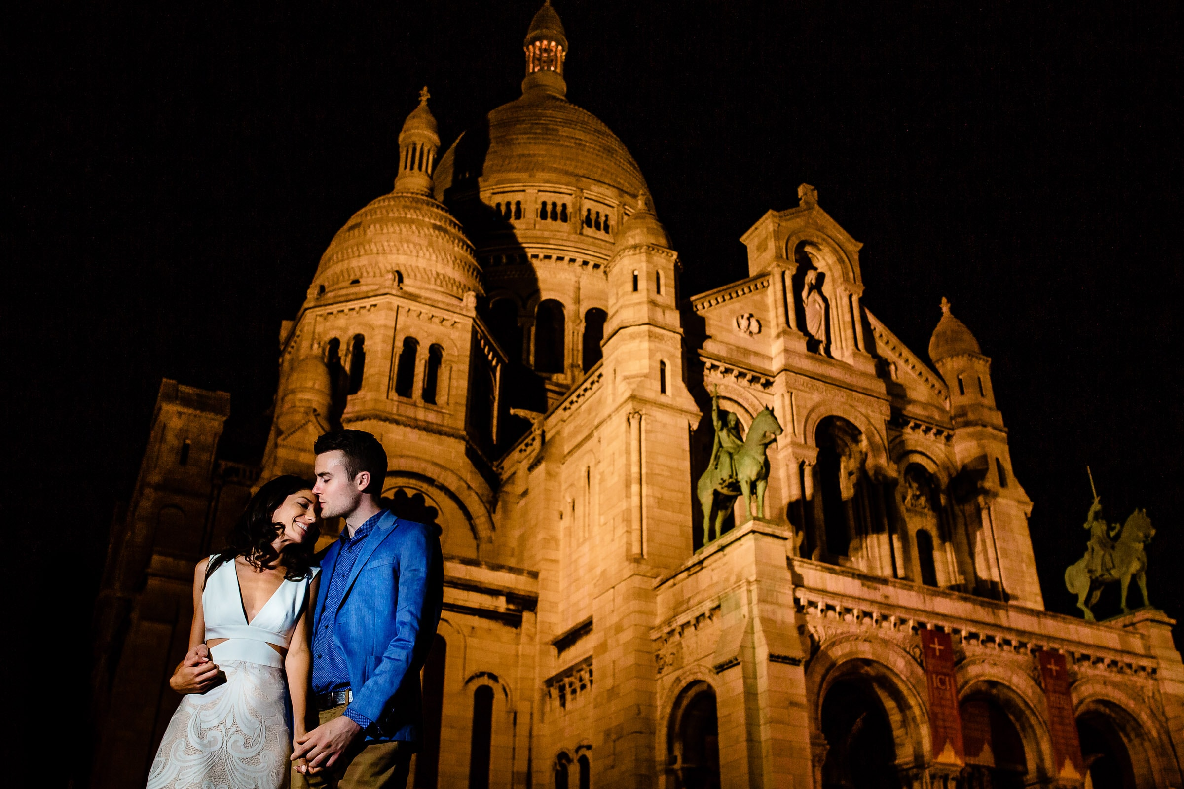 A creative portrait of a couple embracing near Sacre Coeur cathedral during their Paris engagement photos session