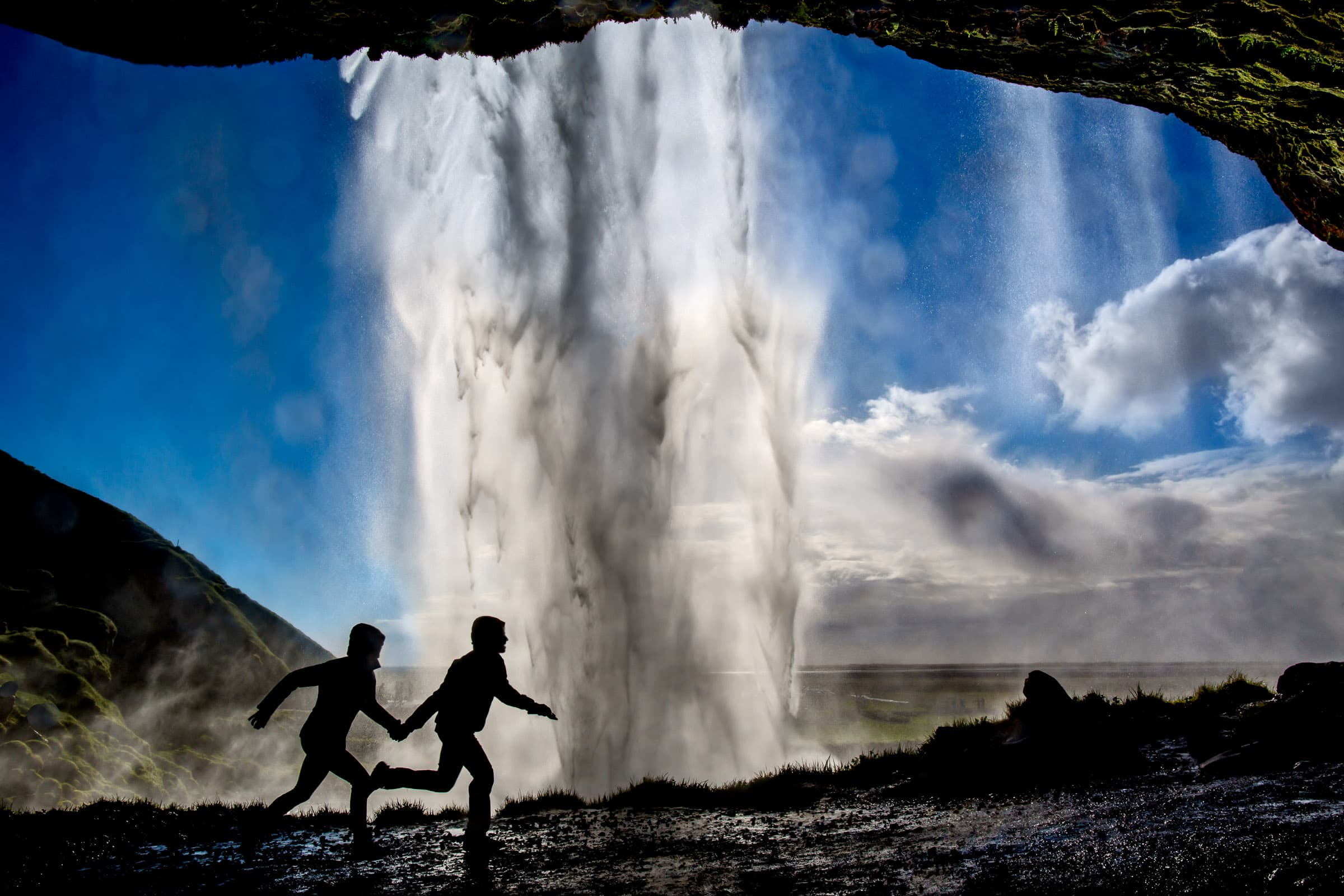 A brilliant photo of an engaged couple running hand and hand under a massive waterfall in Iceland illustrating Jos and Tree's Iceland engagement photo ideas