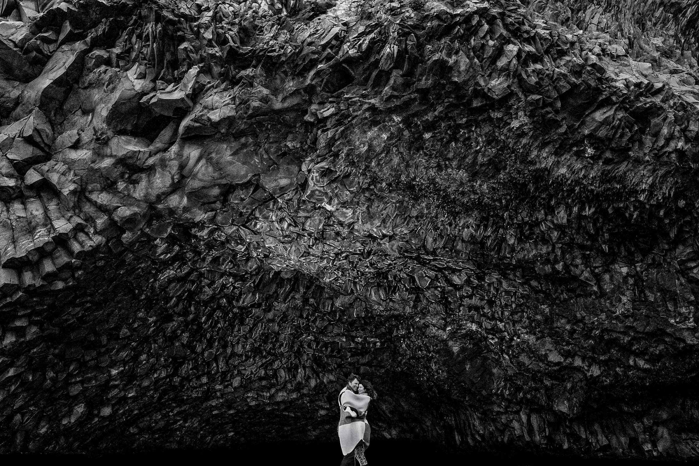 A creative black and white photo of a couple holding each other near massive rocks in Vik, Iceland illustrating Jos and Tree's Iceland engagement photo ideas
