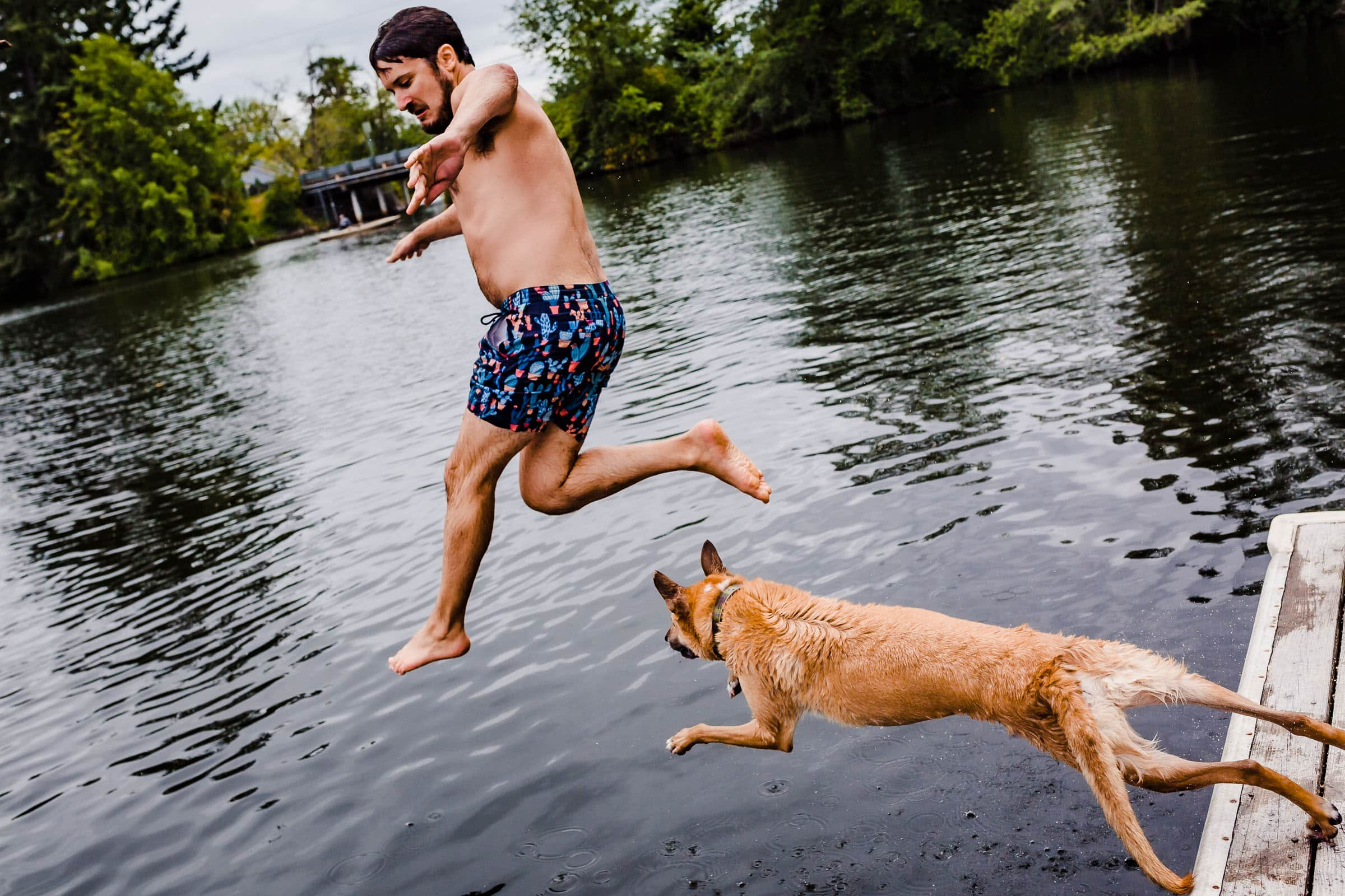 Groom jumping in water before his Seattle Elopement