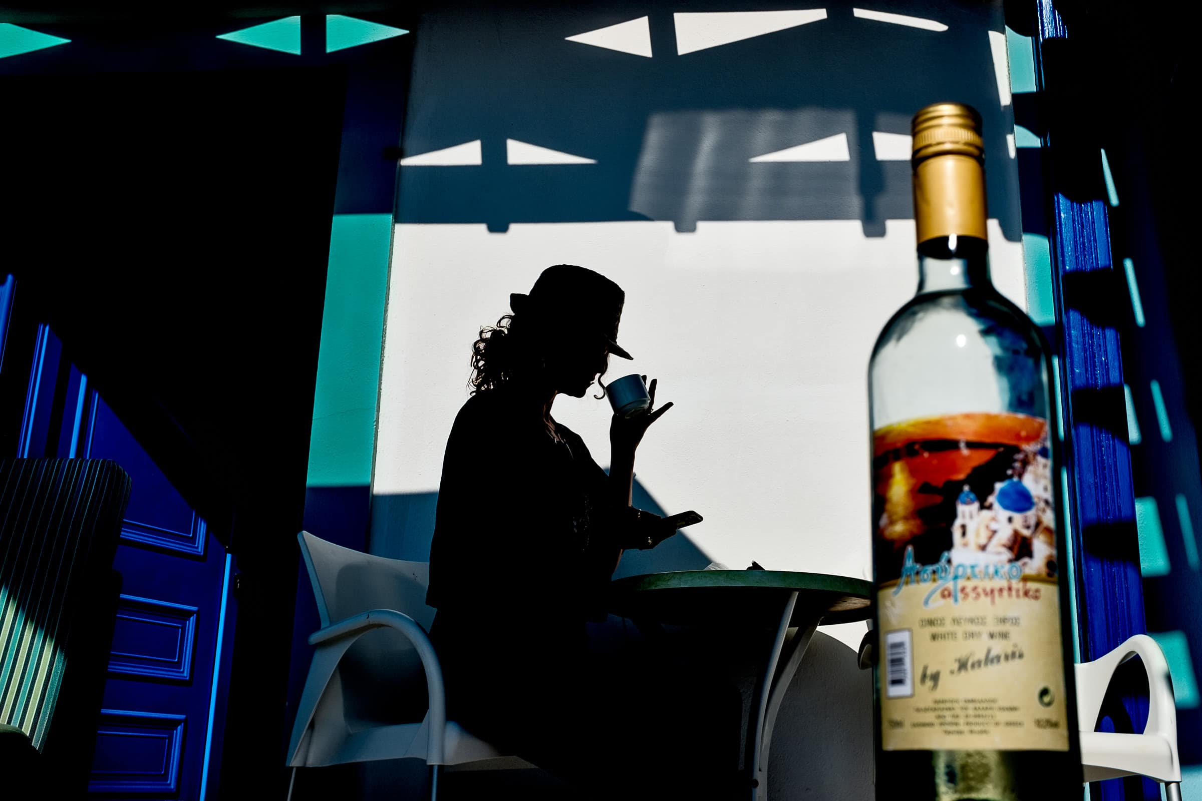 Beautiful silhouette photo of a woman studying Santorini Engagement Photo ideas in Thira, Greece with wine and coffee.