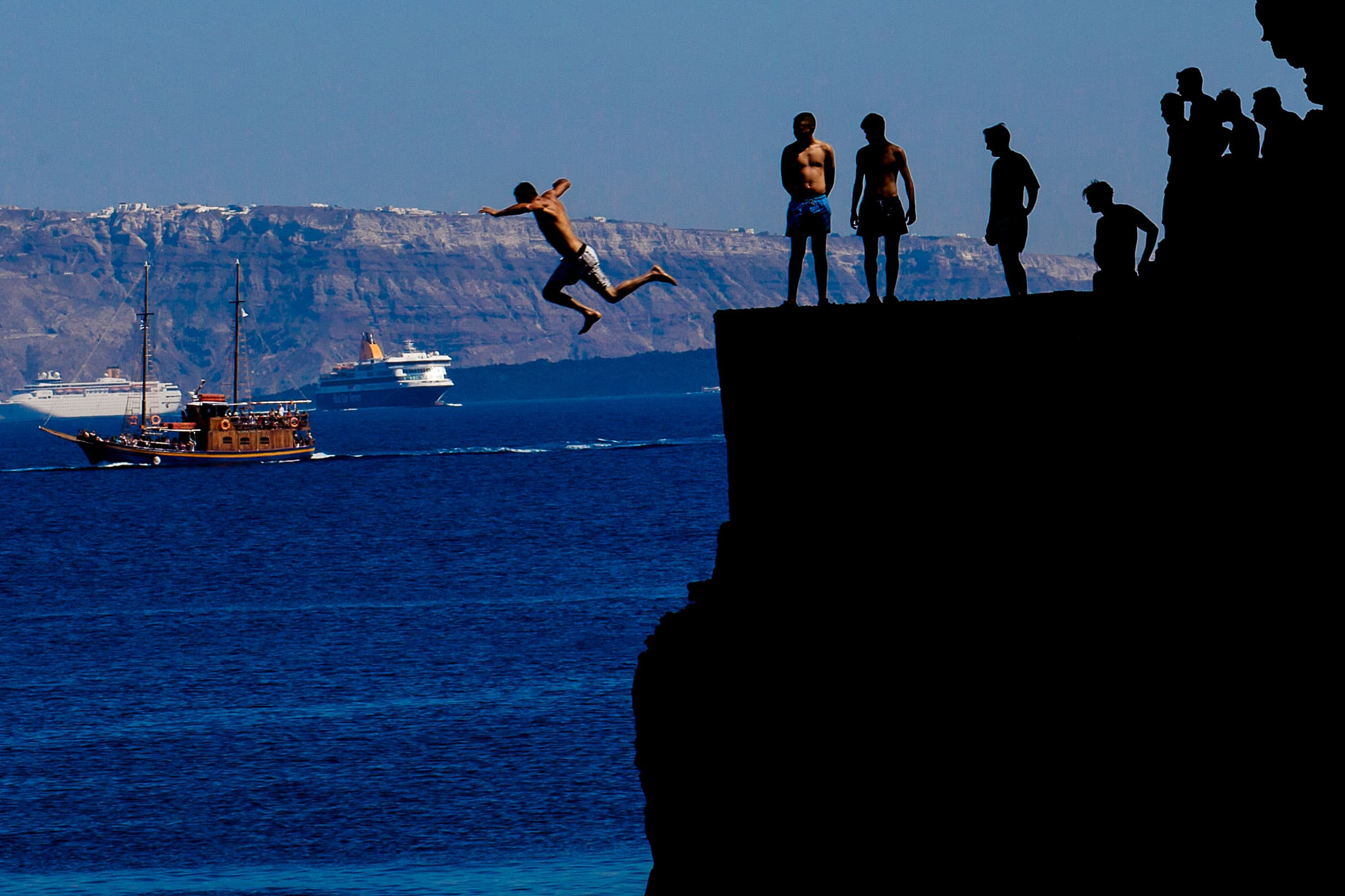 Men jumping of a massive cliff into the ocean while photographers are exploring Santorini Greece Engagement photo ideas