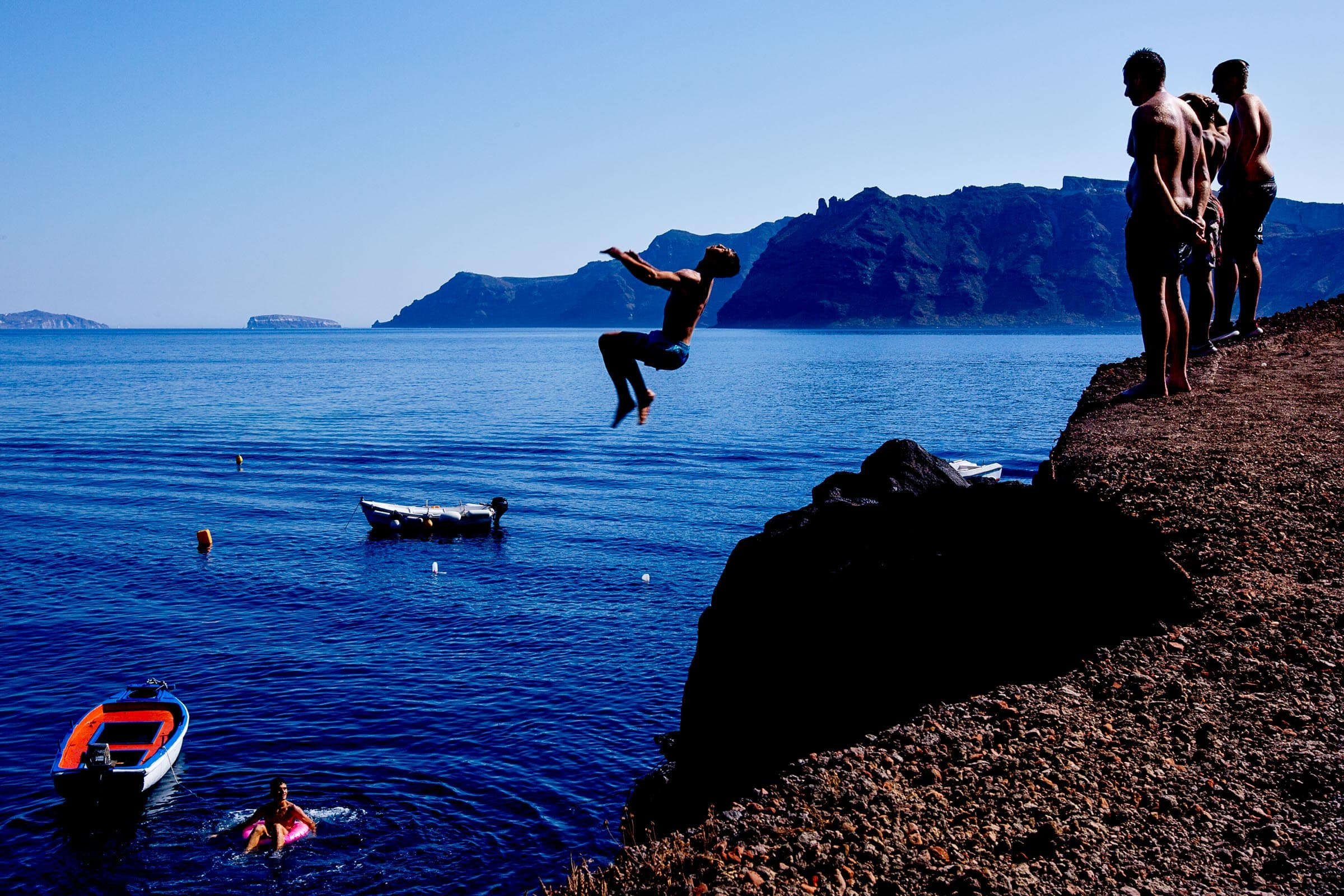 Men flipping backwards of a massive cliff into the ocean while photographers are exploring Santorini Engagement photo ideas