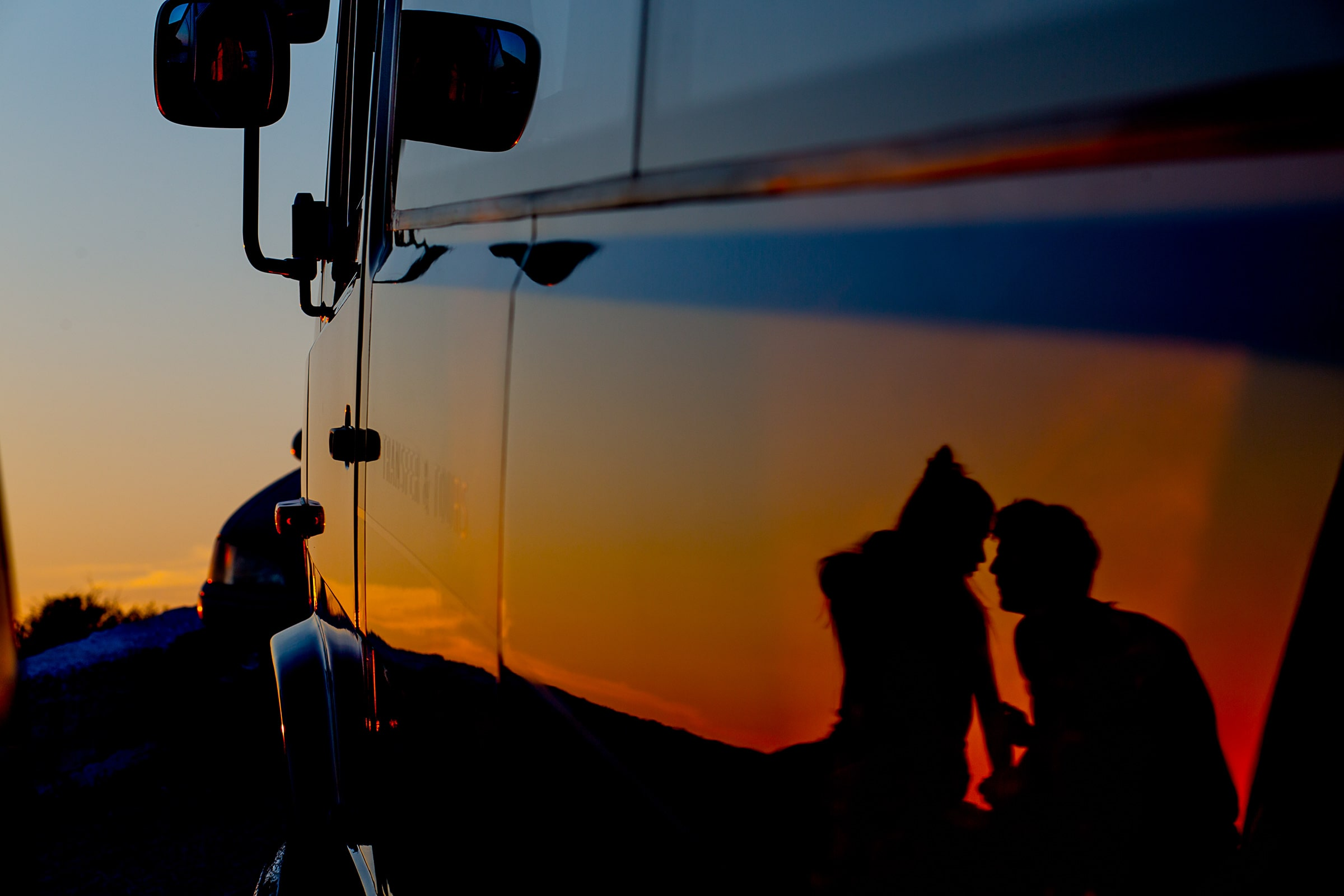 A silhouette of two lovers reflected on a jeep door while photographers Men jumping of a massive cliff into the ocean while photographers are exploring Santorini Engagement photo ideas