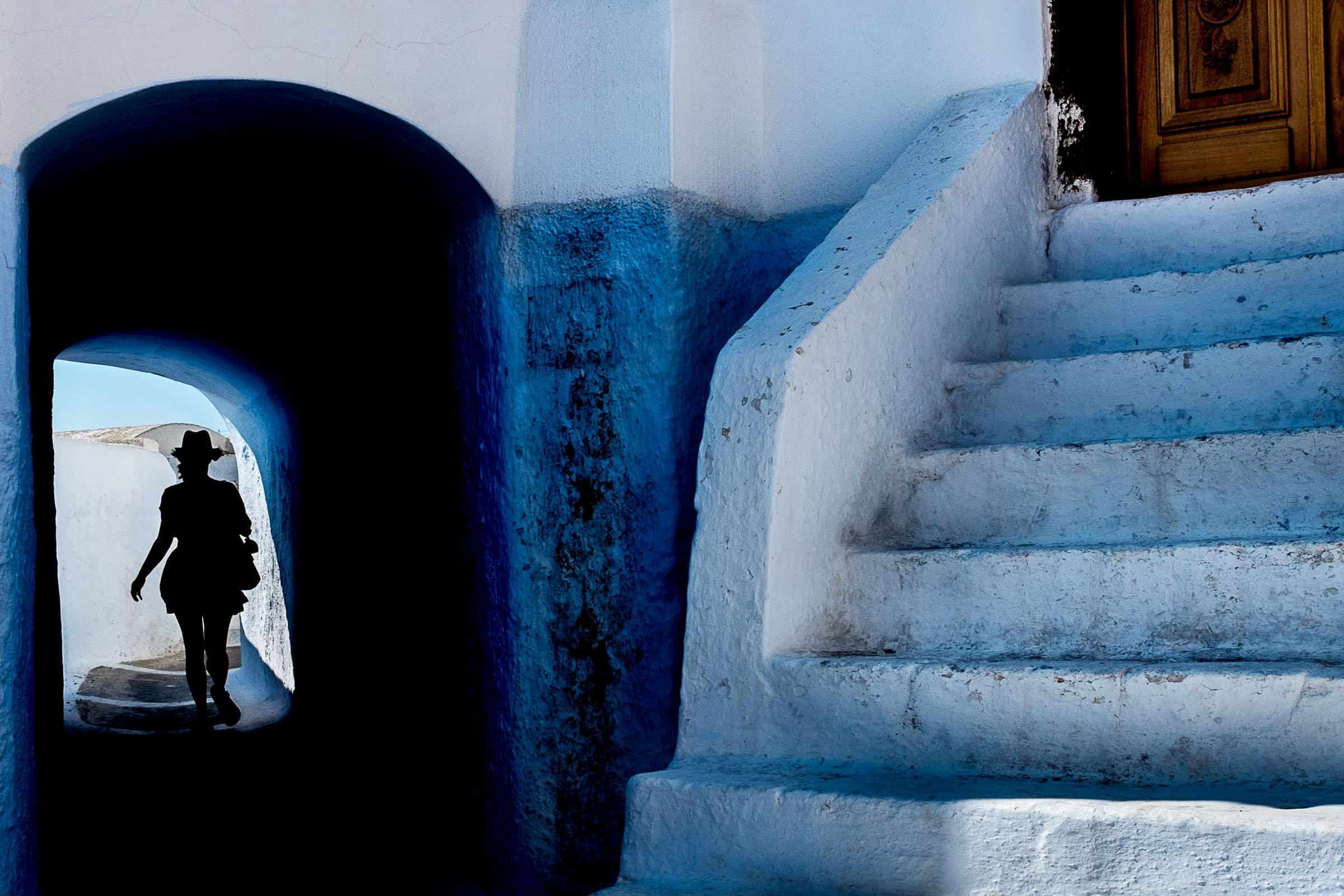Gorgeous story telling silhouette photo of a photographer walking through a tunnel while exploring Santorini Engagement photo ideas