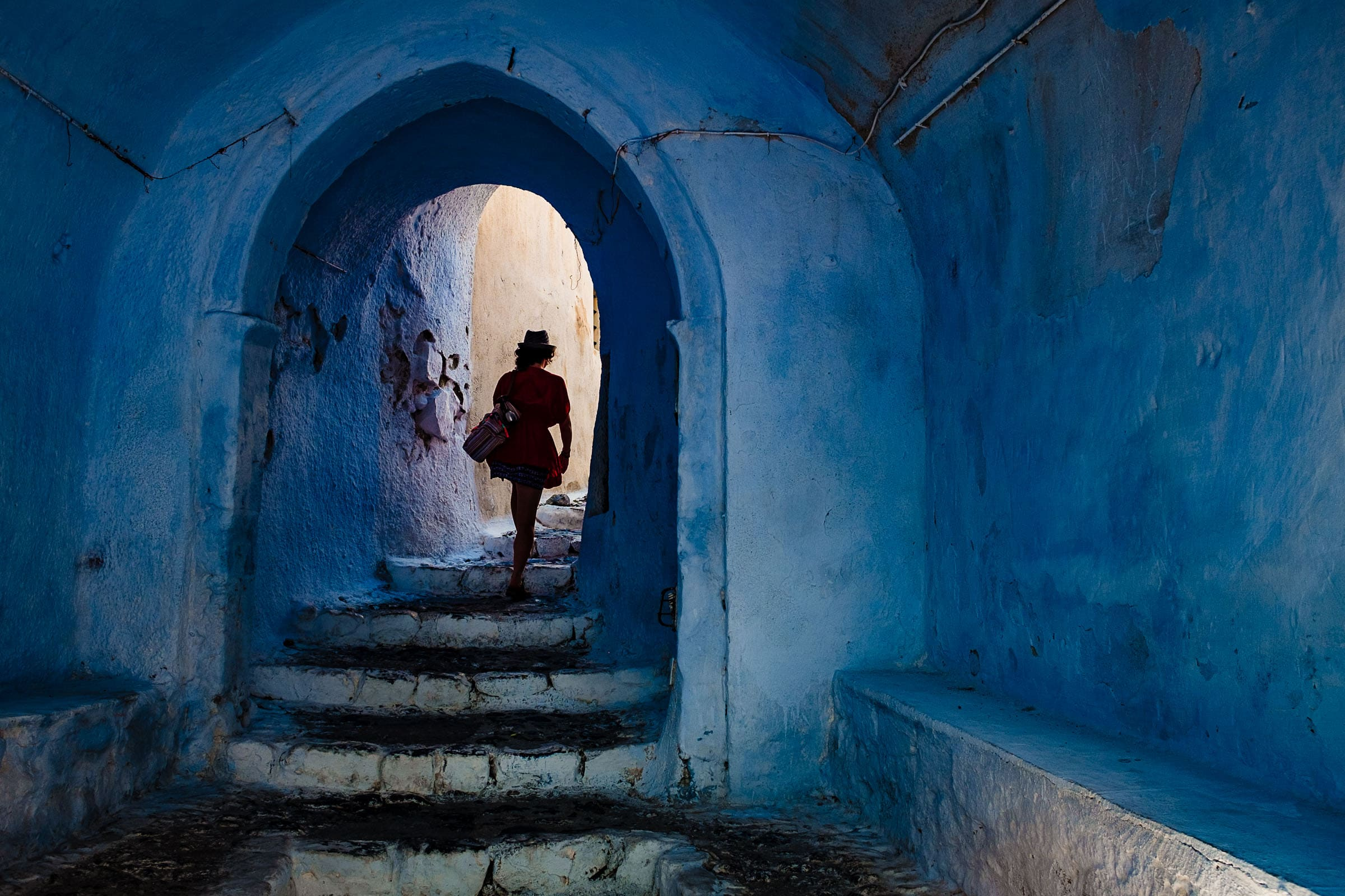 An adventurous photo of a woman walking through the back streets in Greece while exploring Santorini Engagement photo ideas